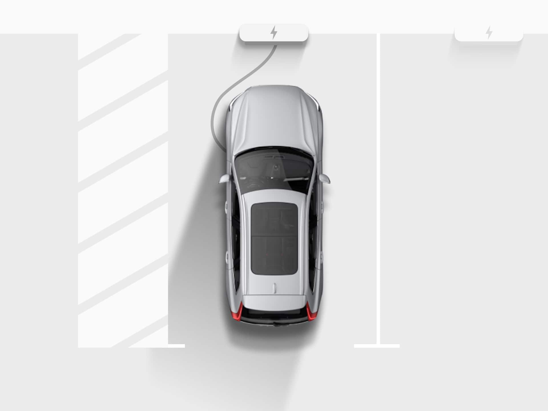 Srebreni potpuno električni SUV Volvo XC40 Recharge prikazan s visine, priključen na stanicu za punjenje na parkirnom mjestu u garaži.