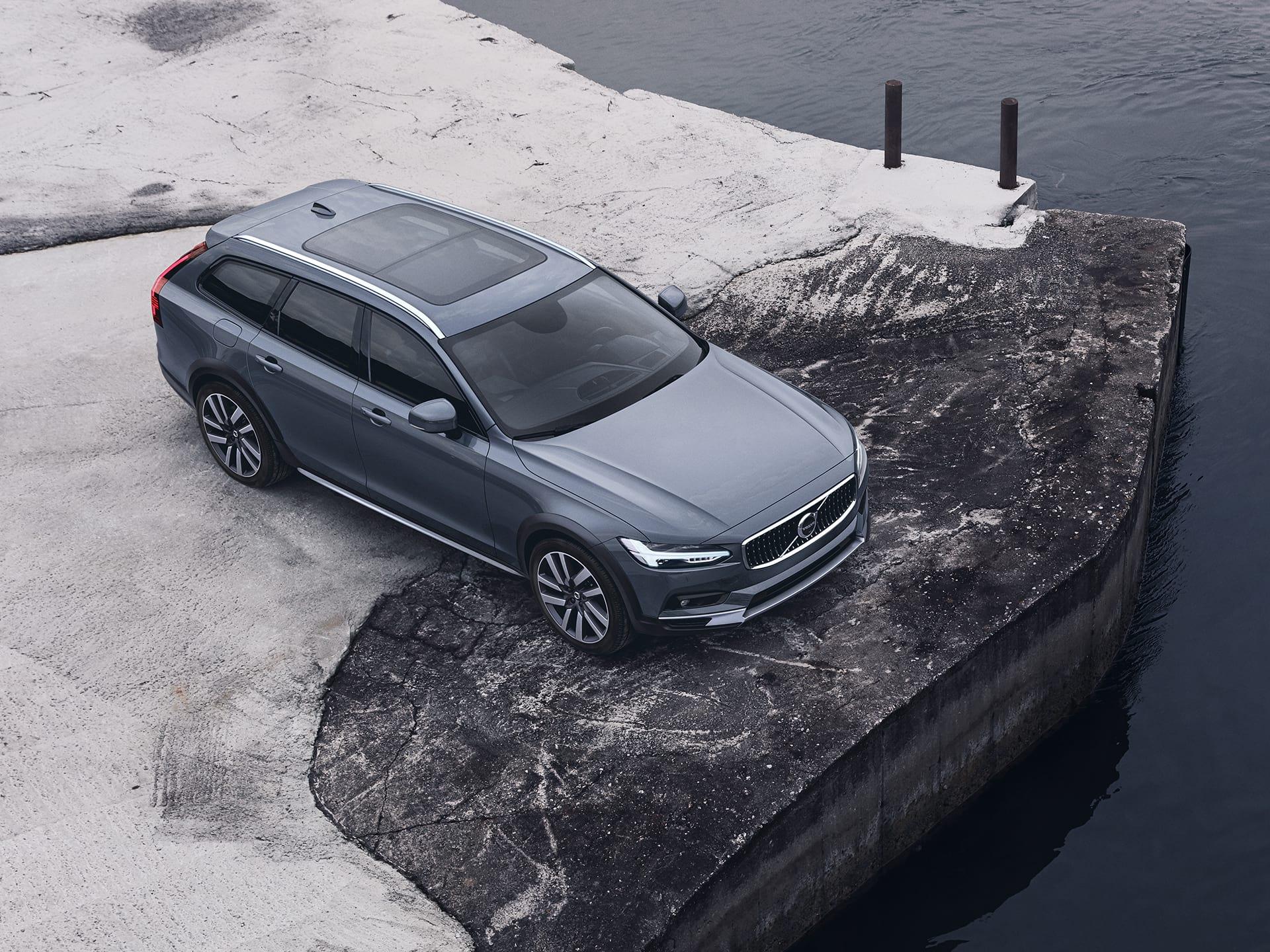 Volvo V90 Cross Country sivoplave boje parkiran na skeli blizu vode.
