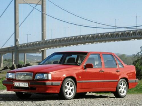 Um Volvo 850 vermelho em frente a uma ponte.