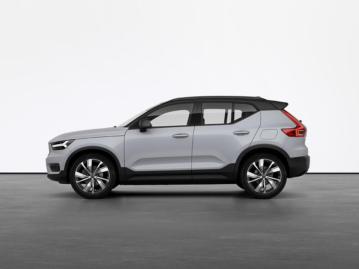 Um Volvo SUV XC40 compacto e 100% elétrico cinza parado em piso cinzento, num estúdio
