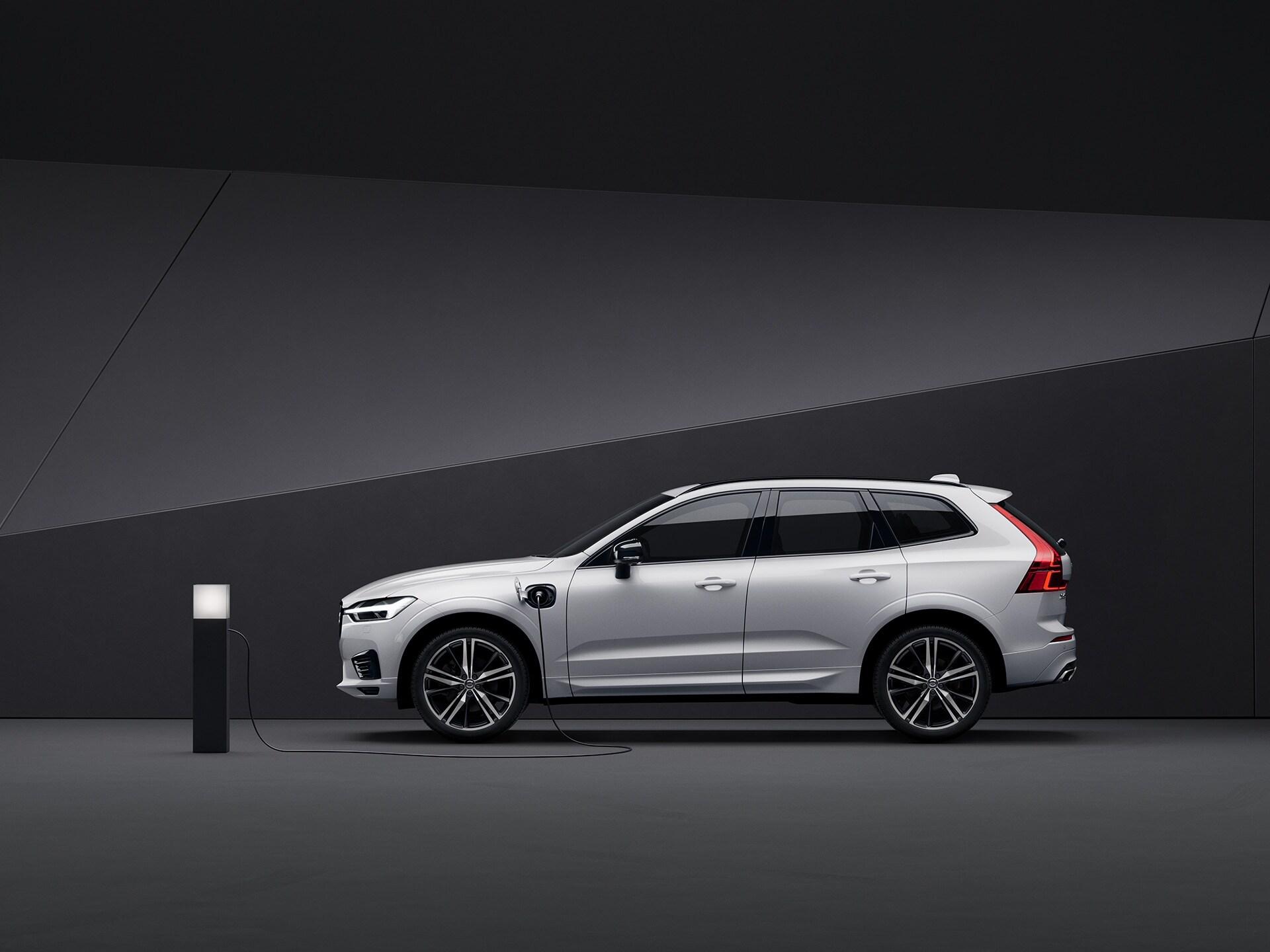 Белый Volvo XC60 Recharge заряжается на черном фоне