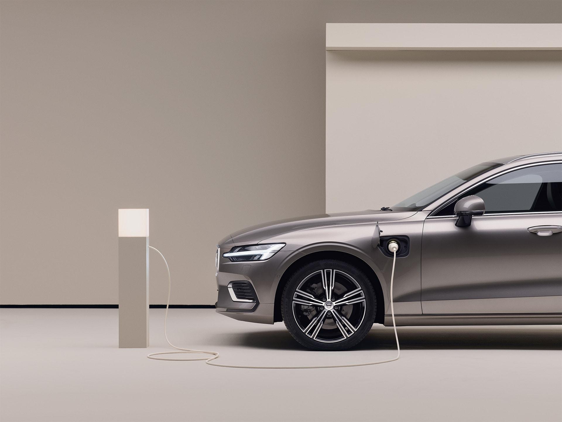 Un Volvo estate gris estacionado se conecta a un punto de carga