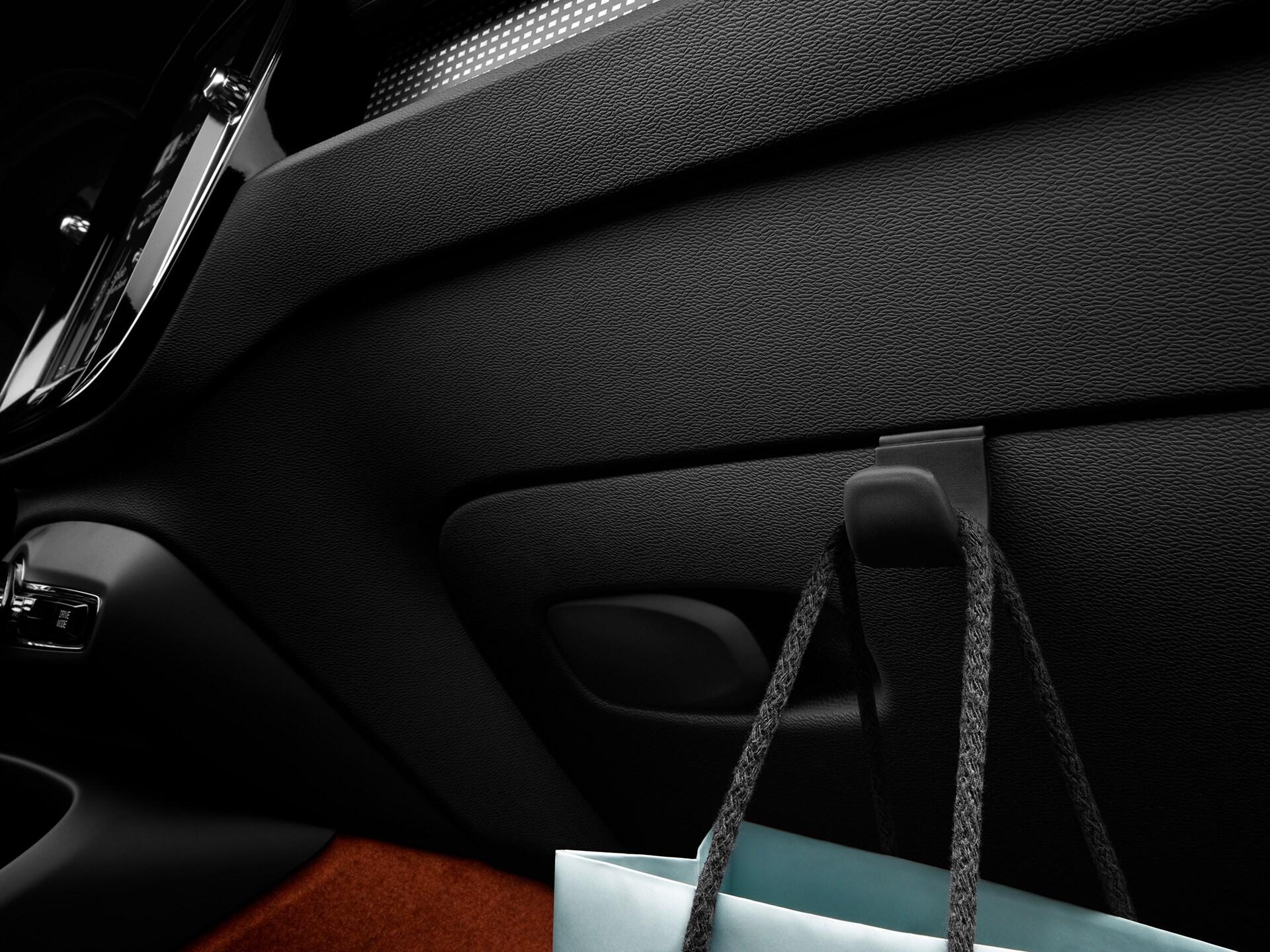 Dentro de un XC40 Recharge híbrido enchufable, hay una bolsa de papel azul dentro del auto