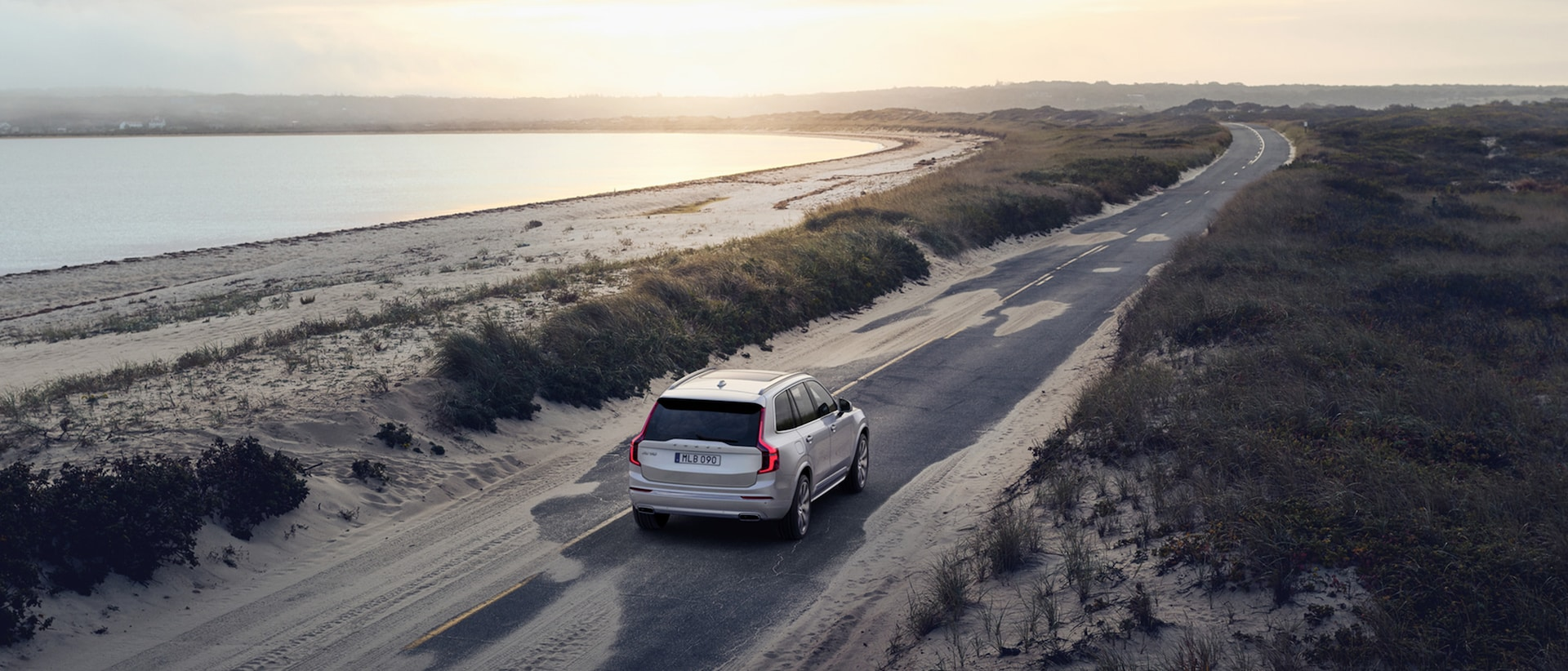 A grey Volvo XC60 is driving on a country road surrounded by open fields at dawn