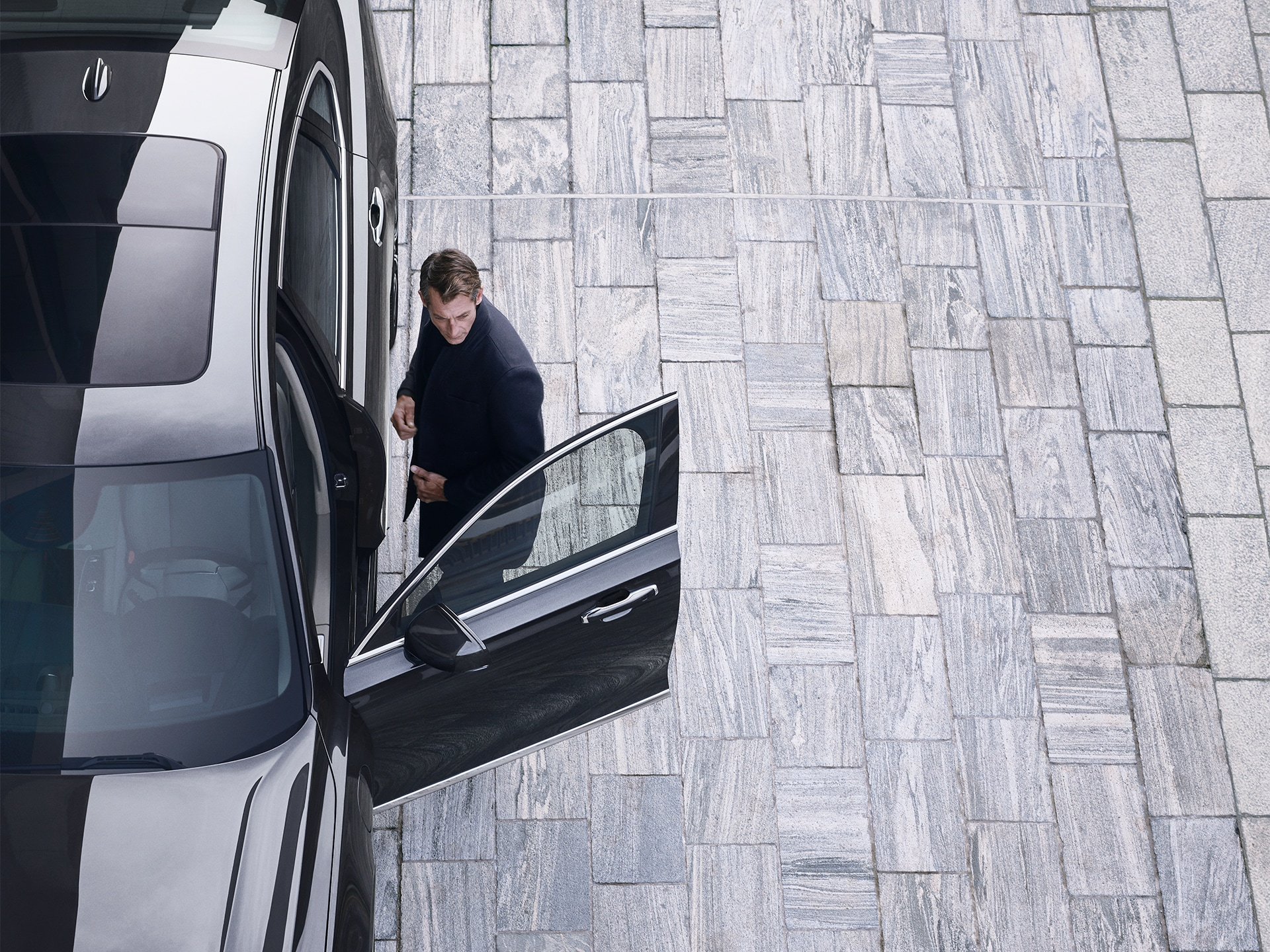 A man is just about to jump into his Volvo S90