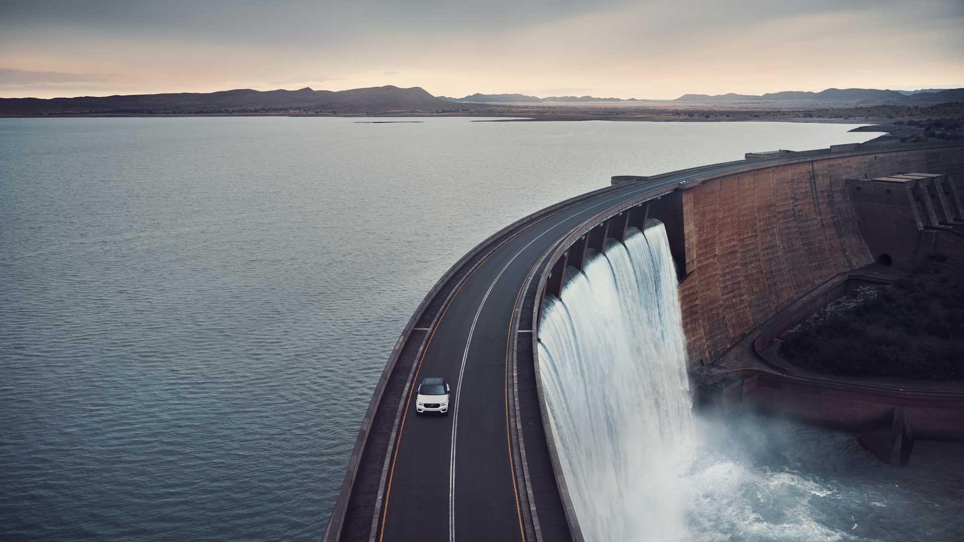 一辆沃尔沃SUV在一座横跨水库的桥上行驶。