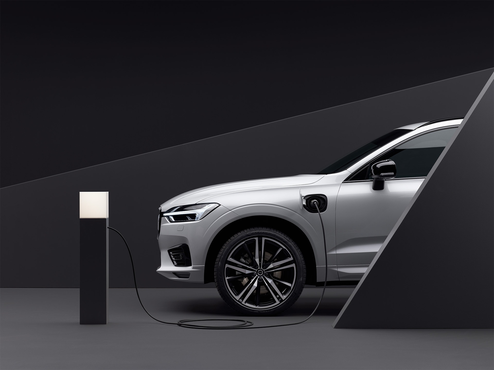 A parked luminous silver Volvo SUV is plugged into a charging point