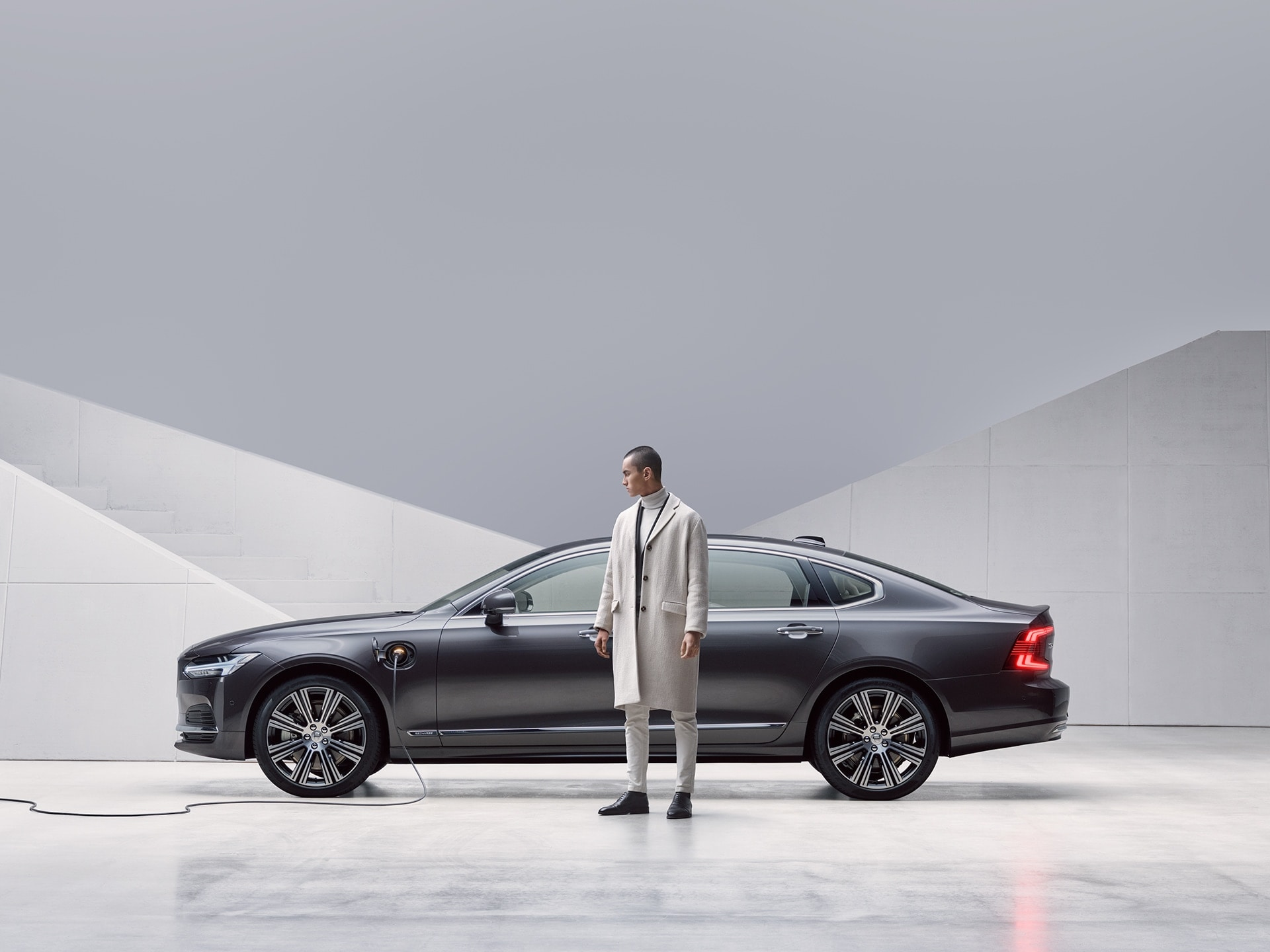 A man is standing in front of his grey Volvo S90, which being charged