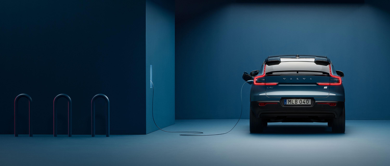 一间深蓝色房间内,停靠着一辆尾部朝前的沃尔沃C40 RECHARGE,正连接一个壁挂式充电桩充电。