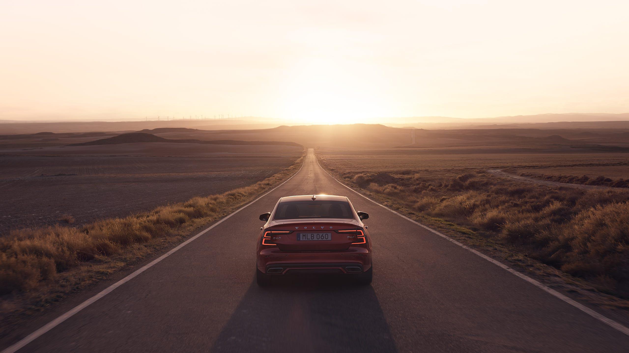 红色沃尔沃 S60 行驶在日落时分的道路上。