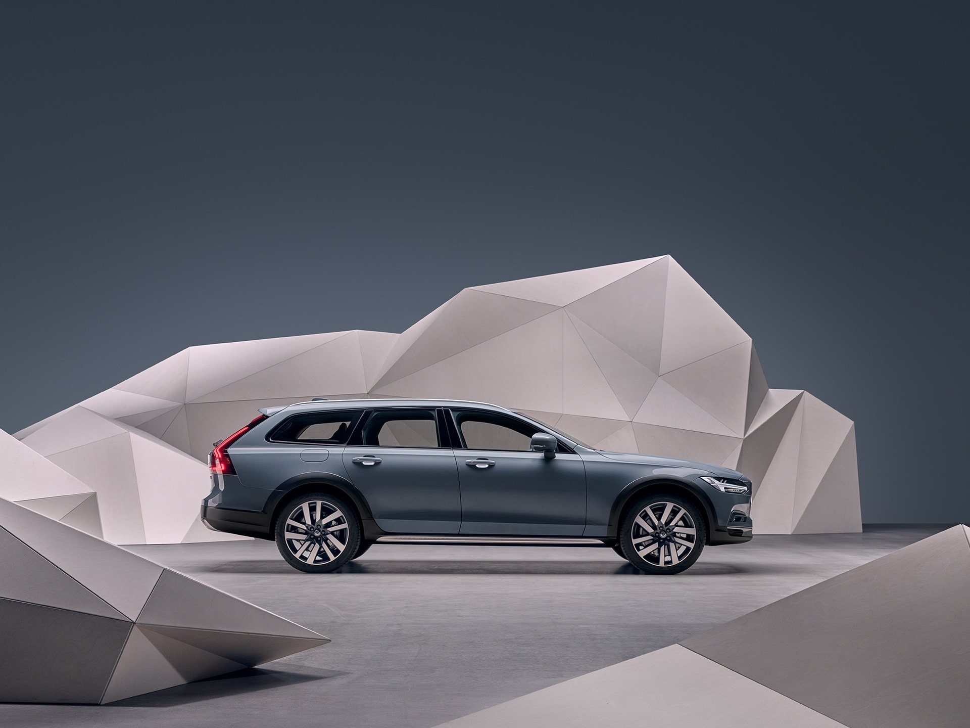 A mussel blue metallic Volvo V90 Cross Country standing in front of an artistic wall