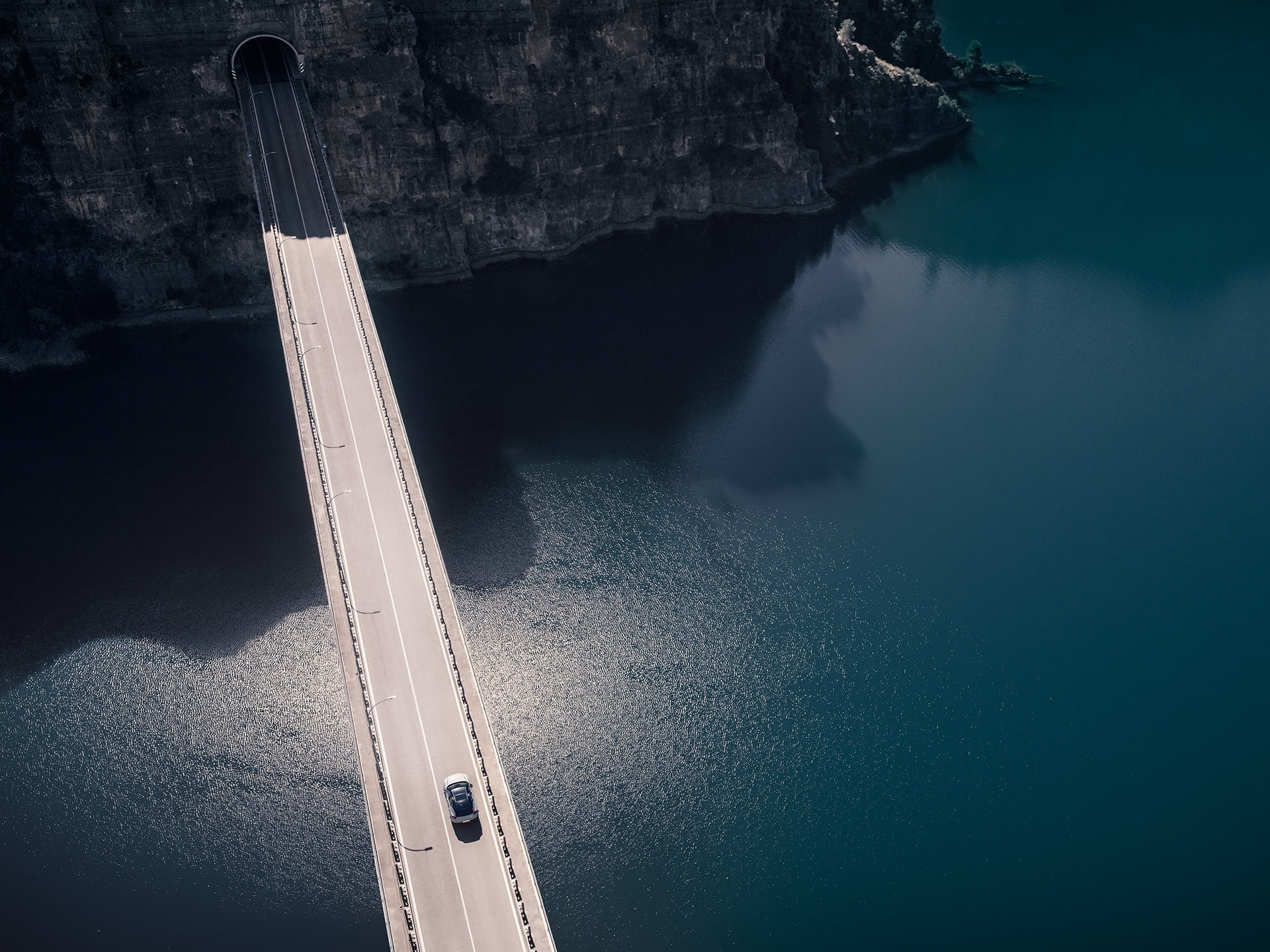 A Volvo XC40 Recharge drives on a bridge over the water that leads into a mountain tunnel.