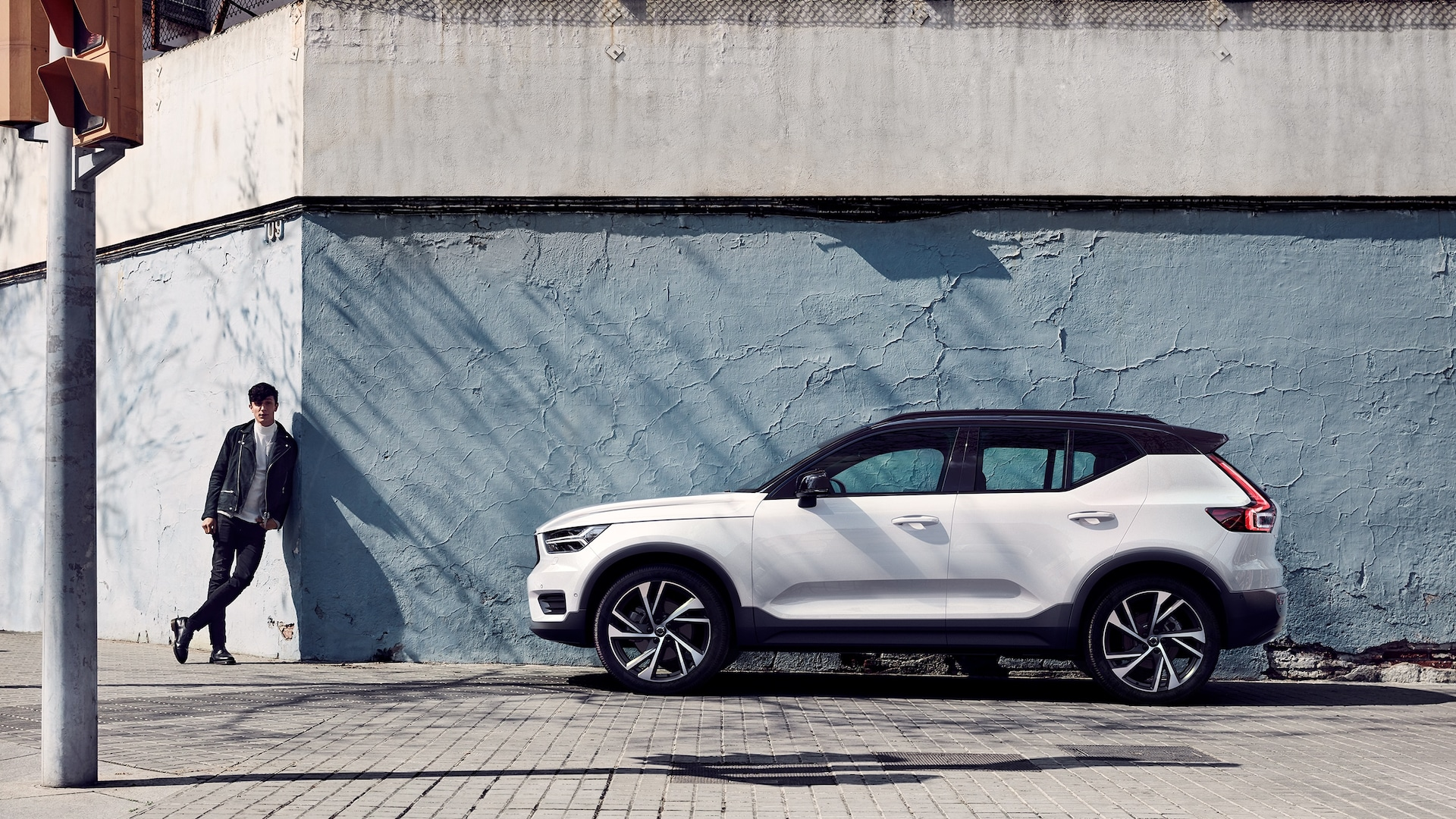 A man stands leaning against a blue concrete facade, next to him is a white Volvo XC40