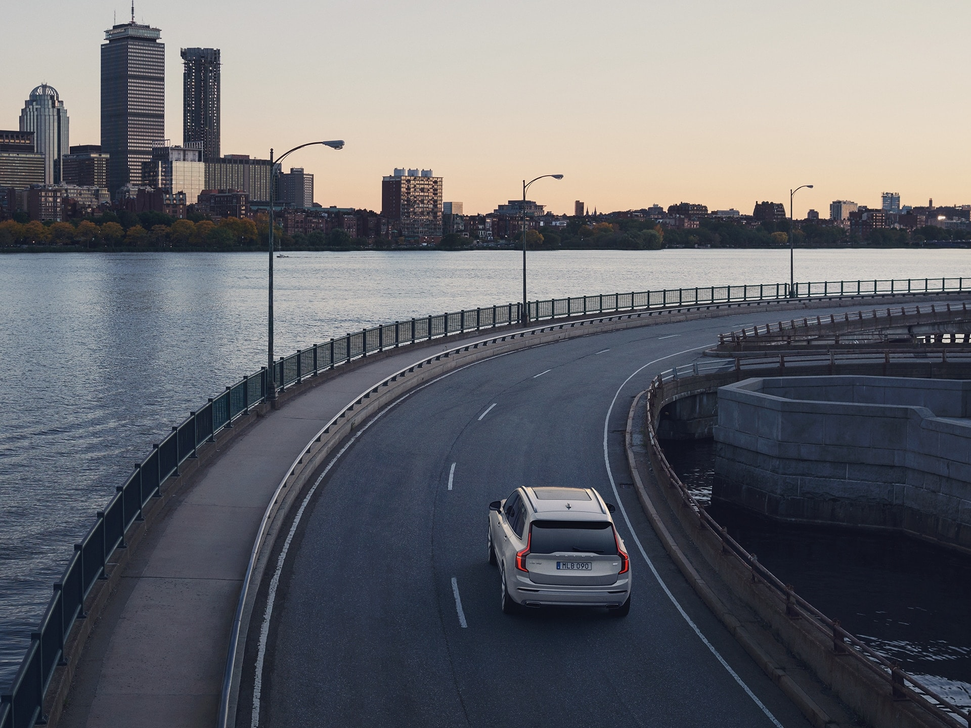 A Volvo XC90 Recharge follows a curve along with the water