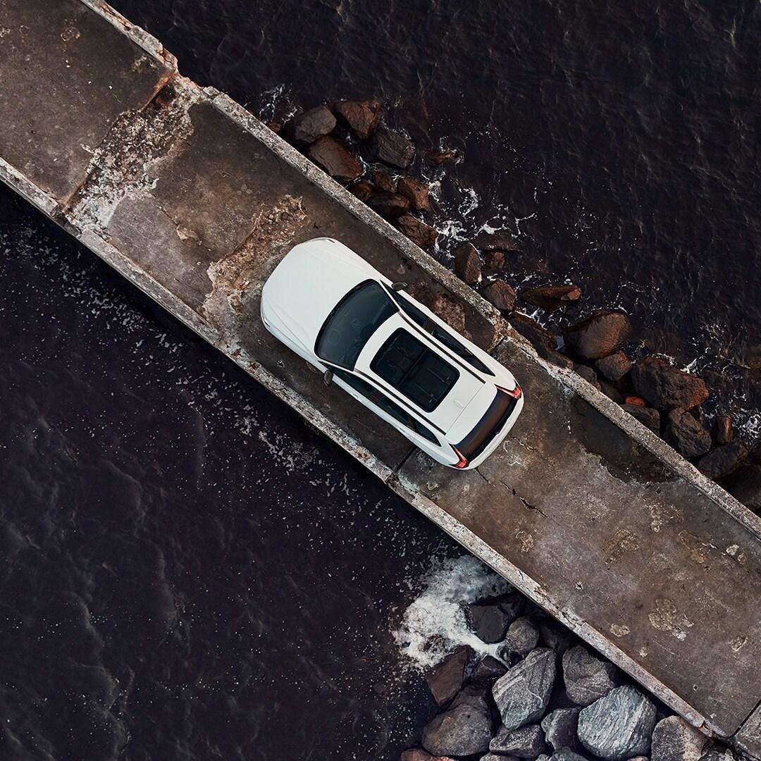 Un Volvo XC60 blanco está estacionado en un muelle rodeada por el mar