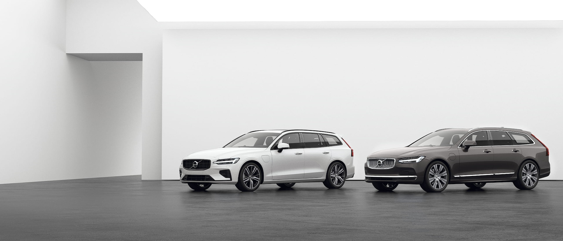 A Volvo Estate V90 and a Volvo Estate V60 Recharge standing on a grey floor