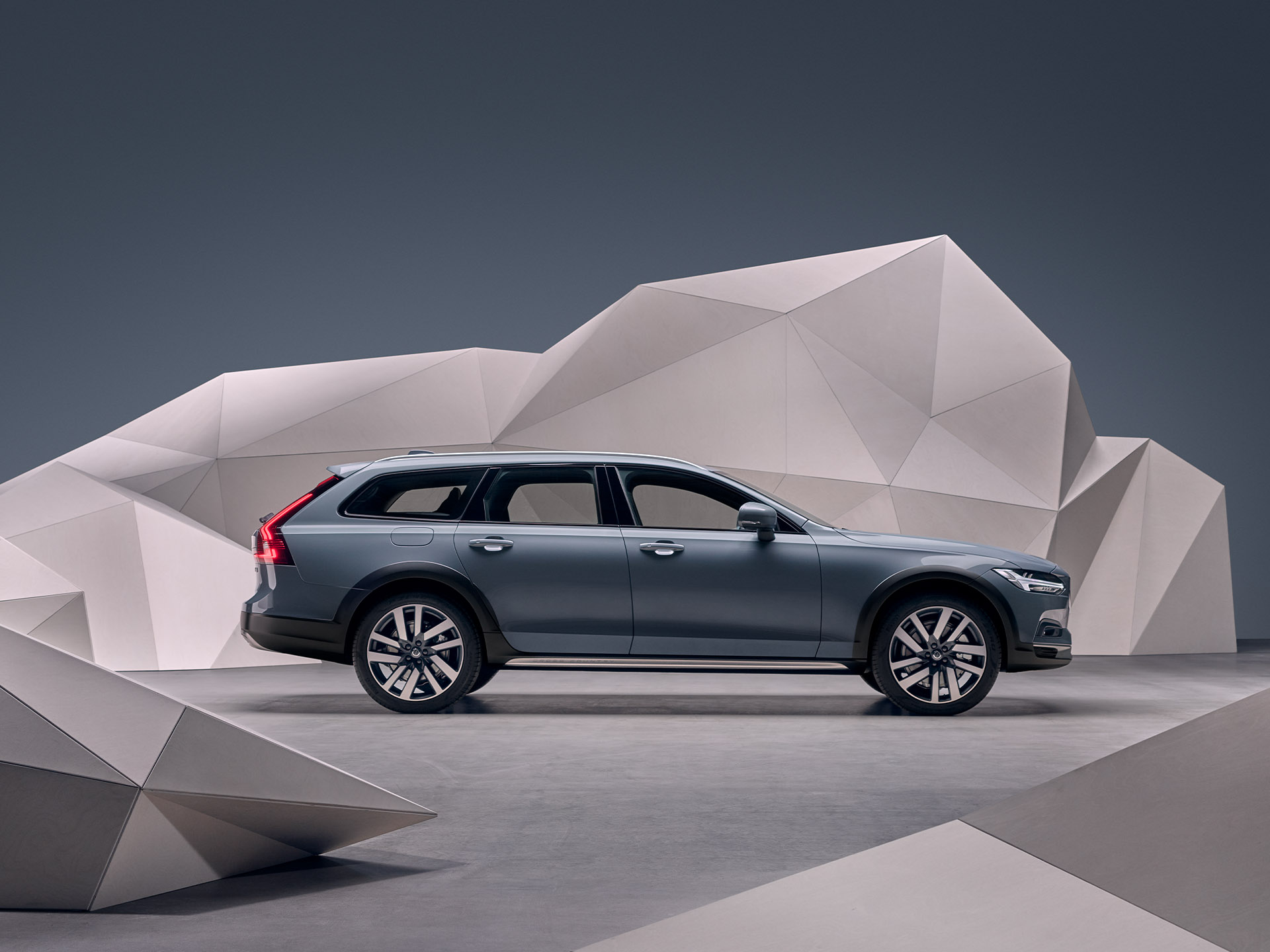 A mussel blue metallic Volvo Estate V90 standing in front of an artistic wall