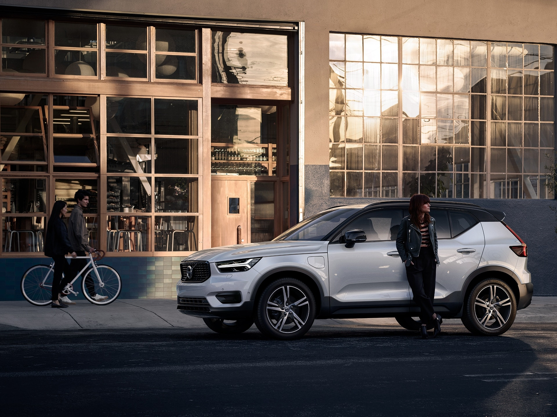 A woman stands leaning against a white XC40 Recharge plug in hybrid, behind her is a restaurant