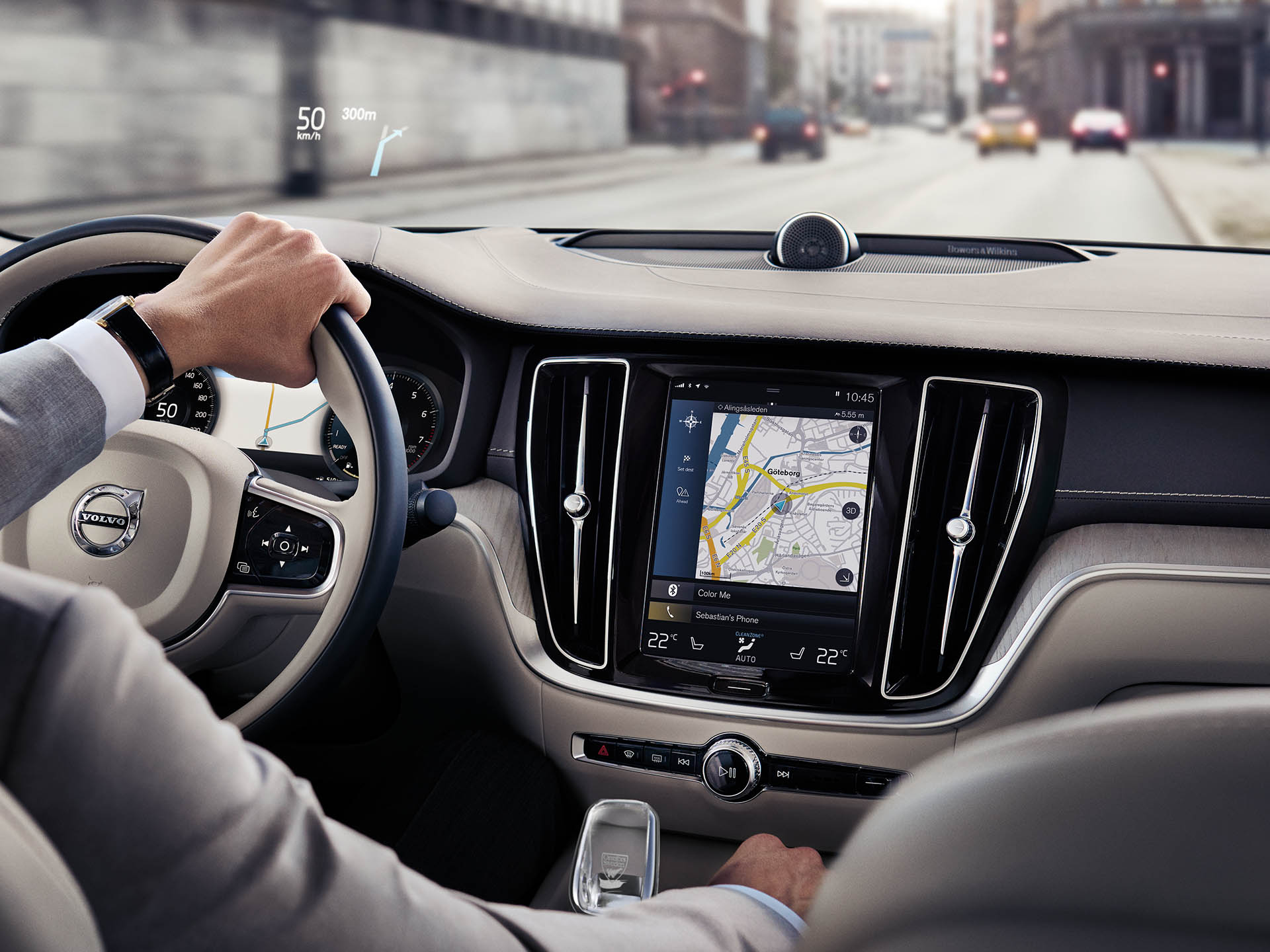 Interiér sedanu Volvo, muž jedoucí po silnici a využívající navigační systém