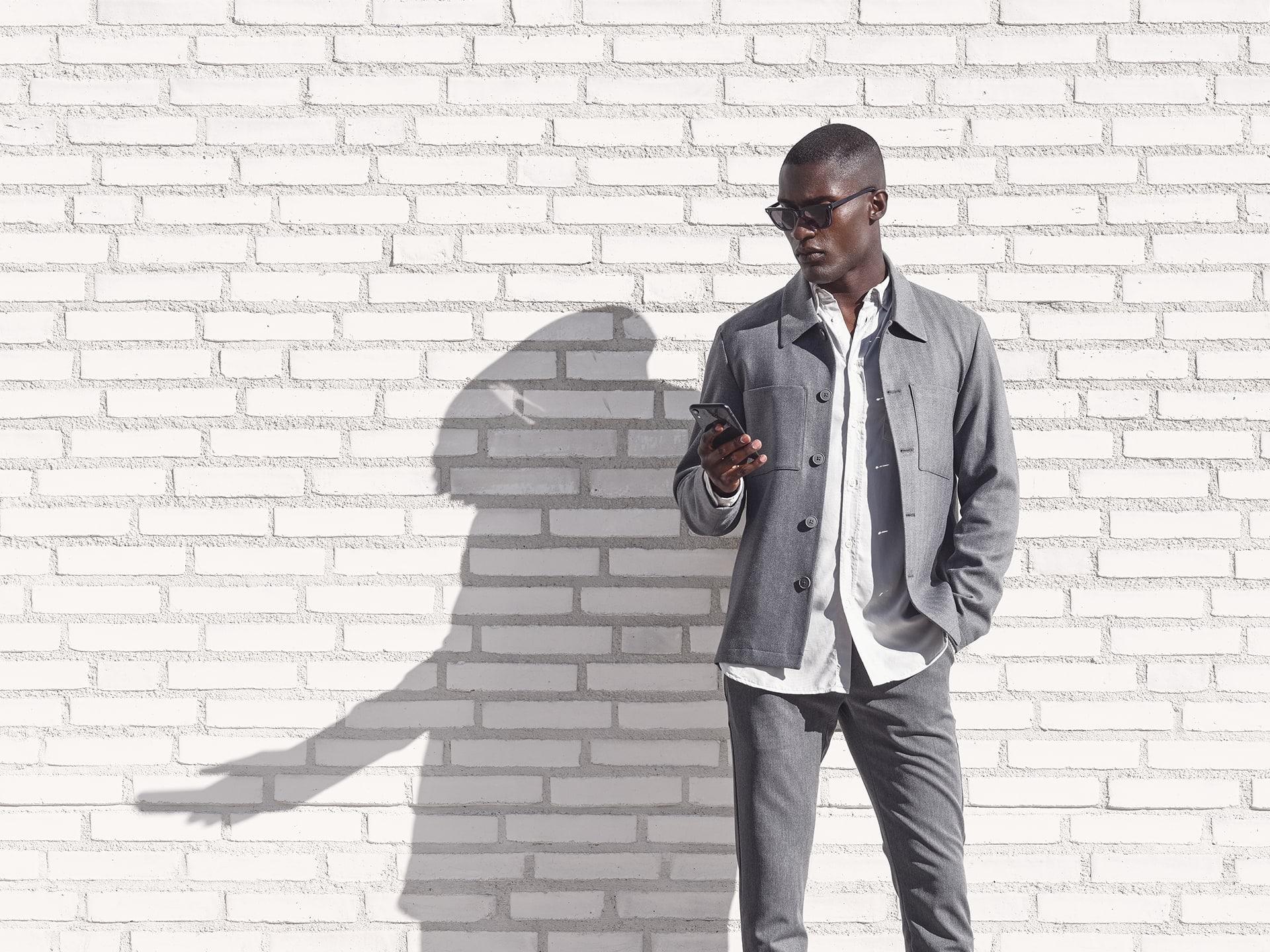 Muž stojící před bílou cihlovou zdi využívající aplikaci Volvo on Call k nastavení teploty ve svém Volvu.