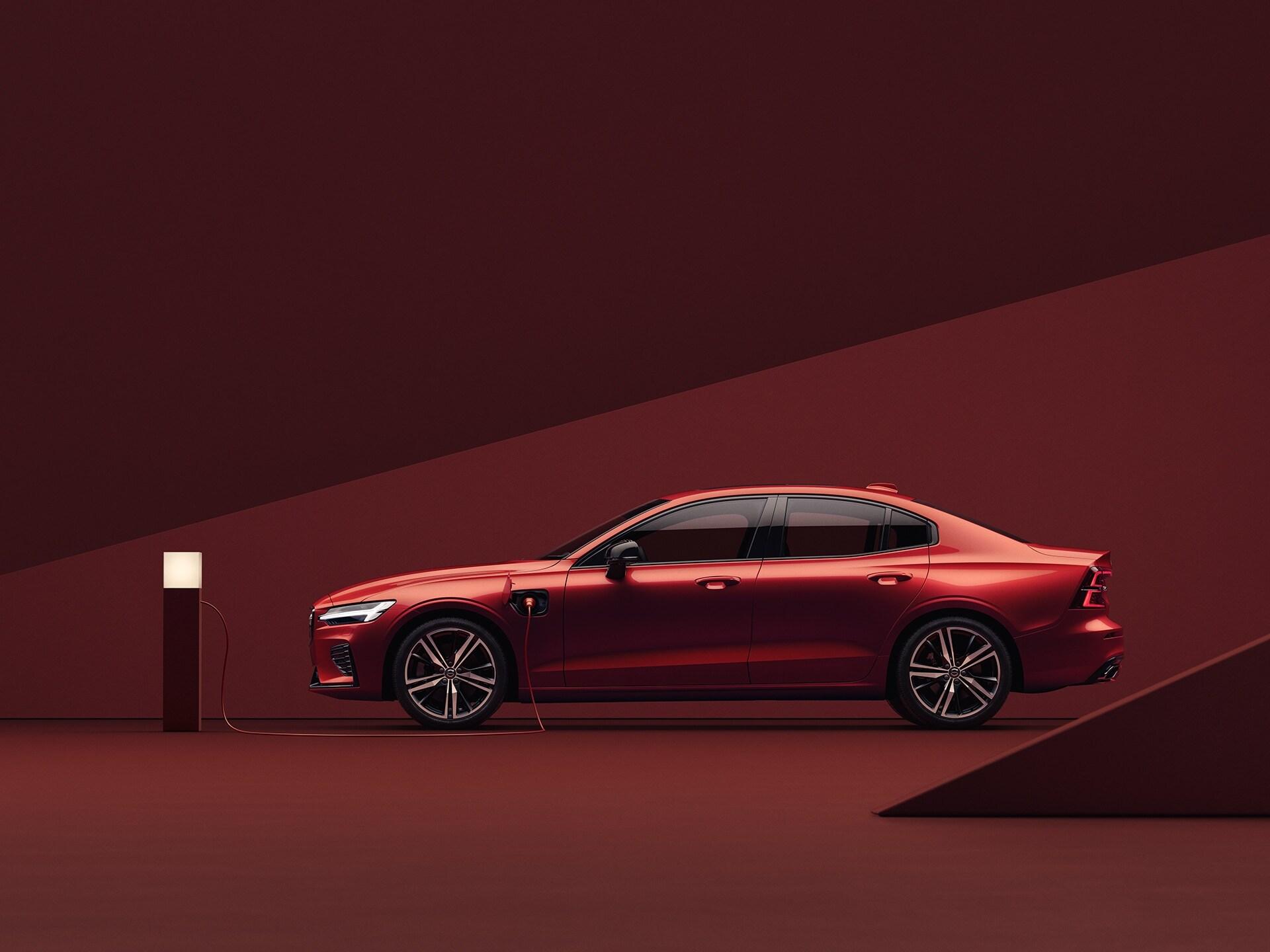 Červené Volvo S60 Recharge při nabíjení v červeném prostředí.