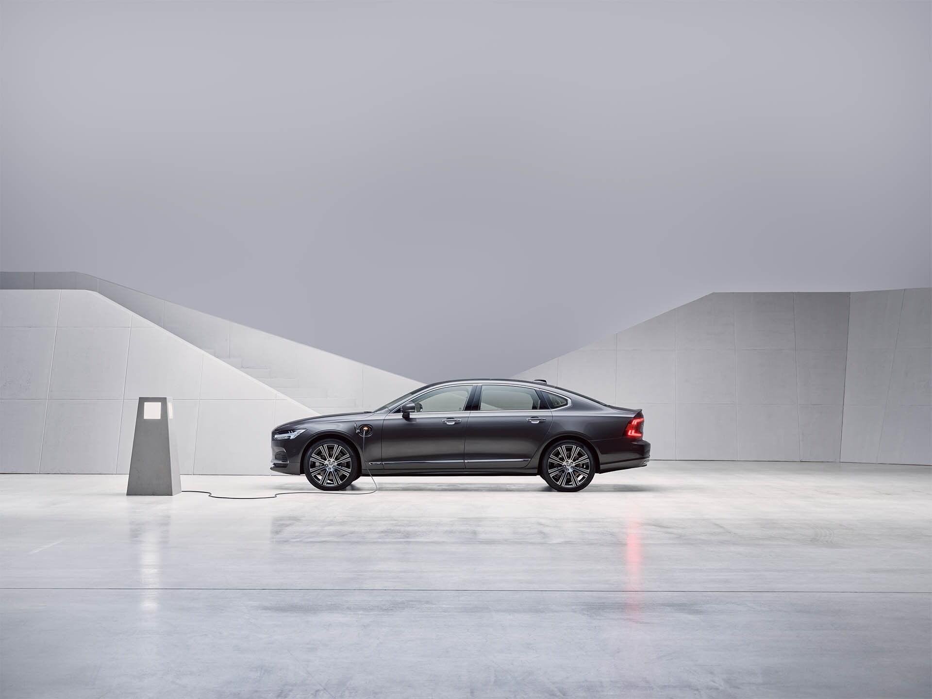 Ein Volvo S90 Plug-in Hybrid sedan (Farbe pebble grey) steht still und wird aufgeladen