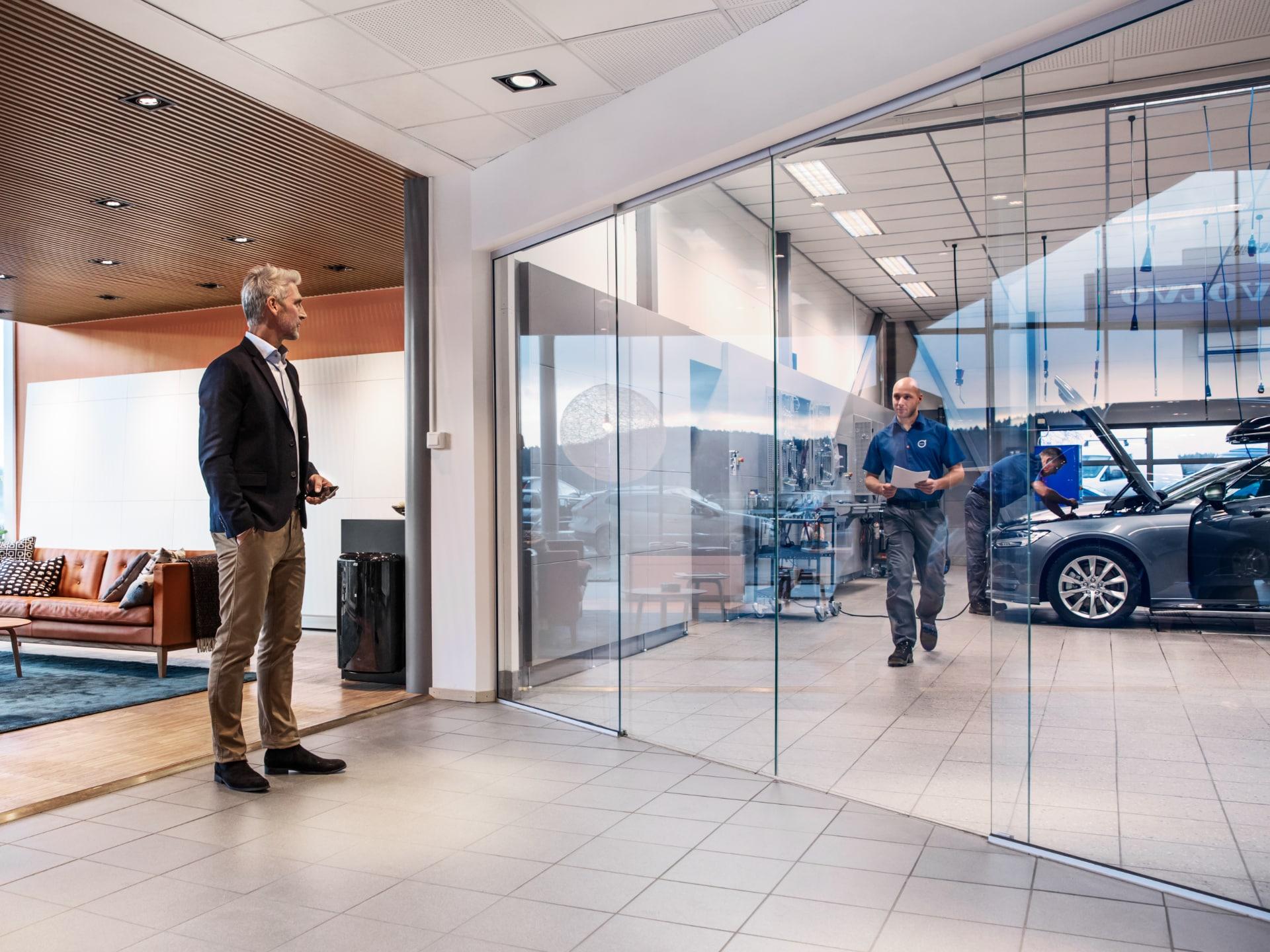 Ein Mann steht im Wartebereich der Volvo-Werkstatt.