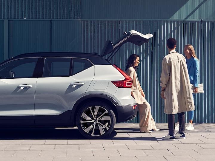 Drei Erwachsene stehen vor einem bzw. lehnen sich an einen Volvo XC40 mit geöffneter Heckklappe vor einer blaugrünen Fassade.