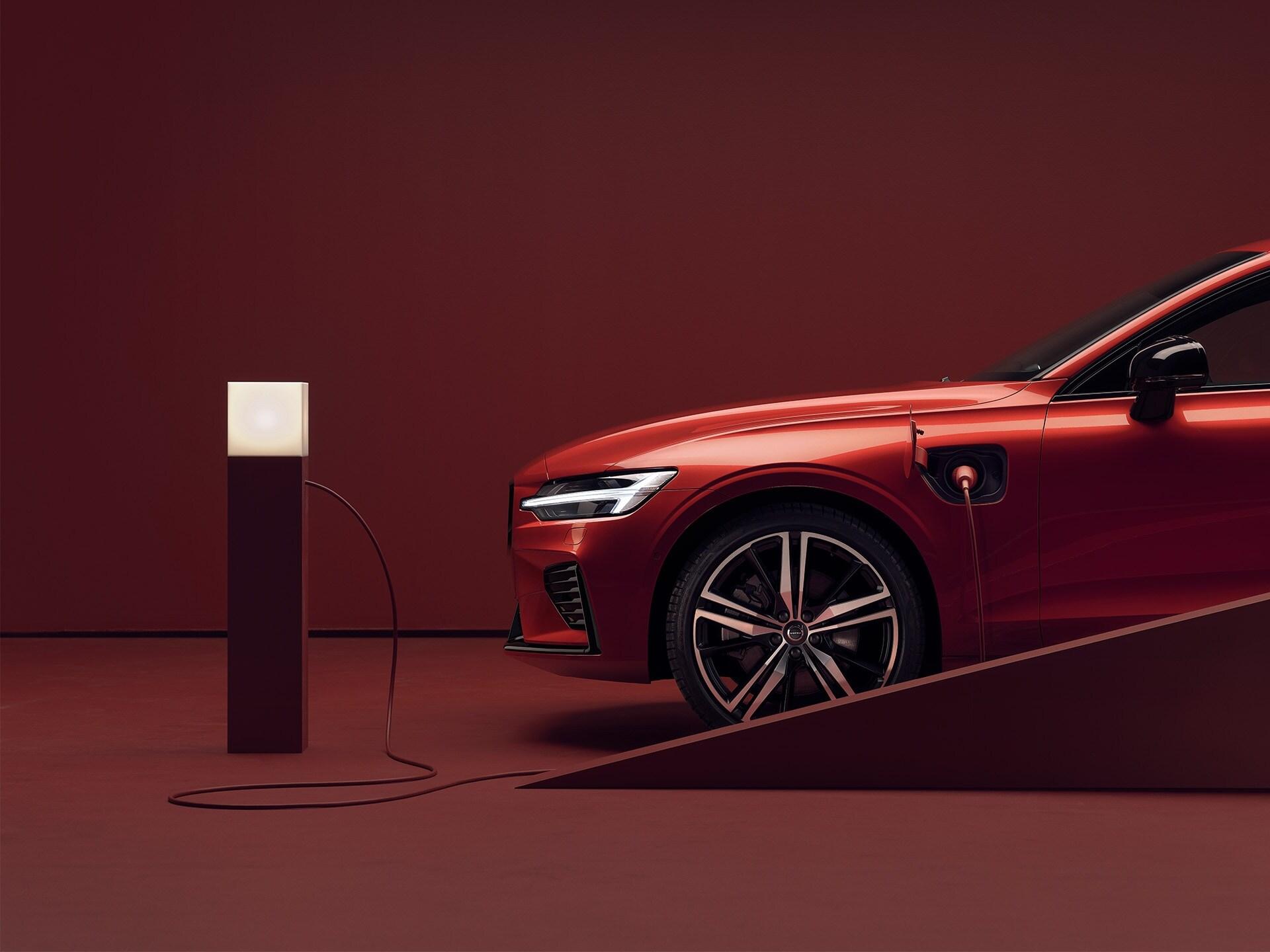 Eine geparkte rote Volvo Limousine ist an eine Ladestation angeschlossen
