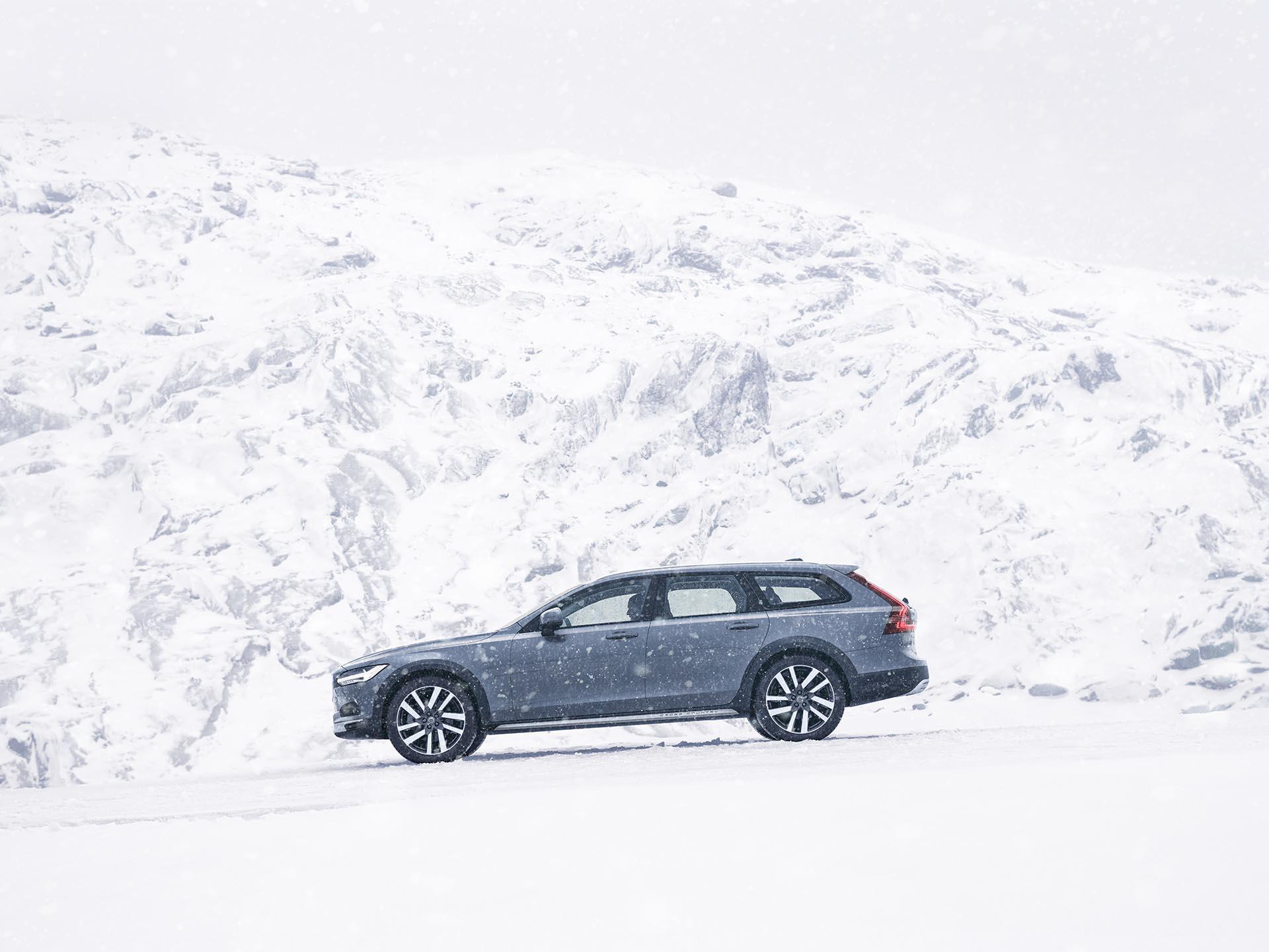 Ein Volvo V90 Cross Country-Kombi in der Lackierung Mussel Blue fährt durch verschneite Berge