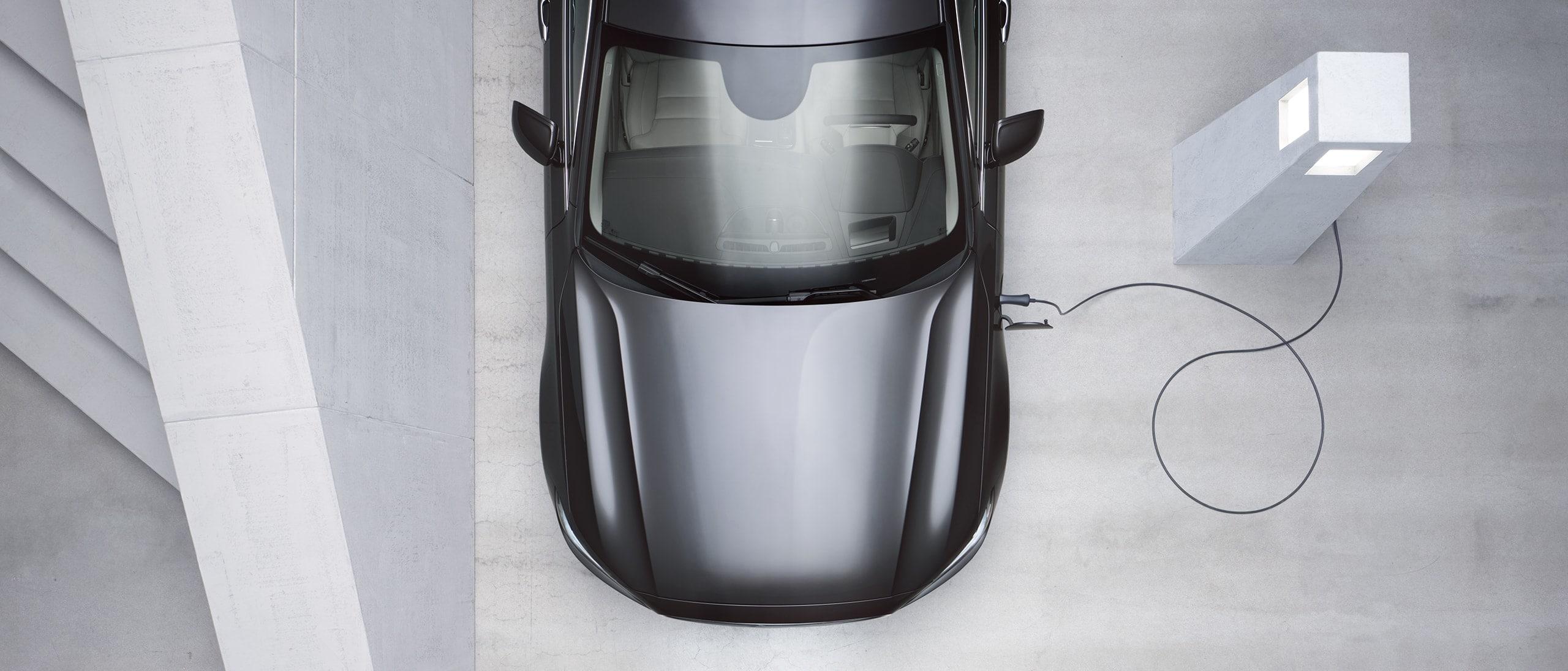 Ein grauer Volvo-Pkw von oben, der an einer Ladestation aufgeladen wird