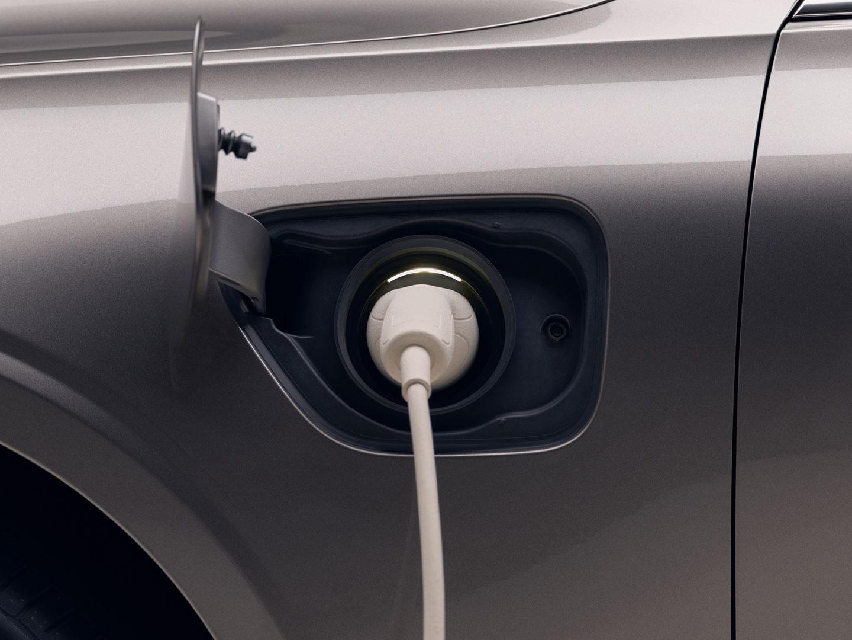 Eine Nahaufnahme eines Ladekabels, dass am Ladeanschluss eines Volvo Recharge-Fahrzeugs eingesteckt ist.