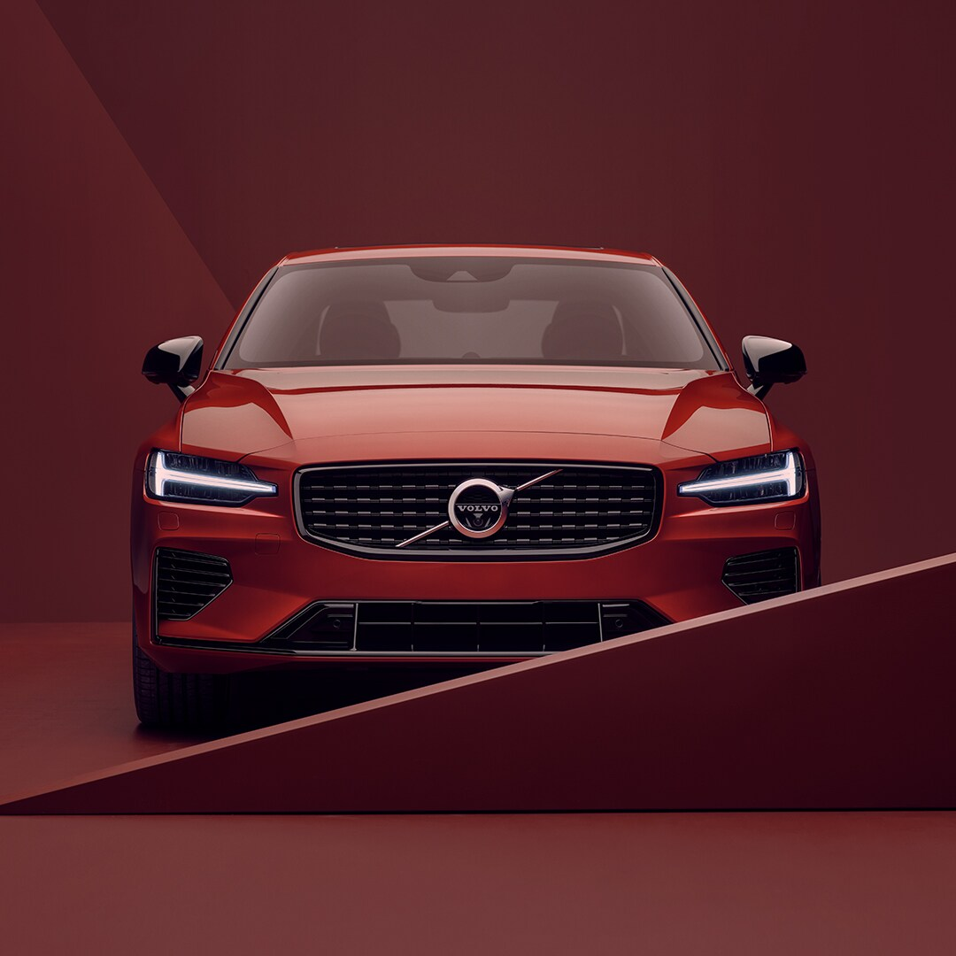 Das vordere Exterieur eines roten Volvo S60 Recharge in roter Umgebung.