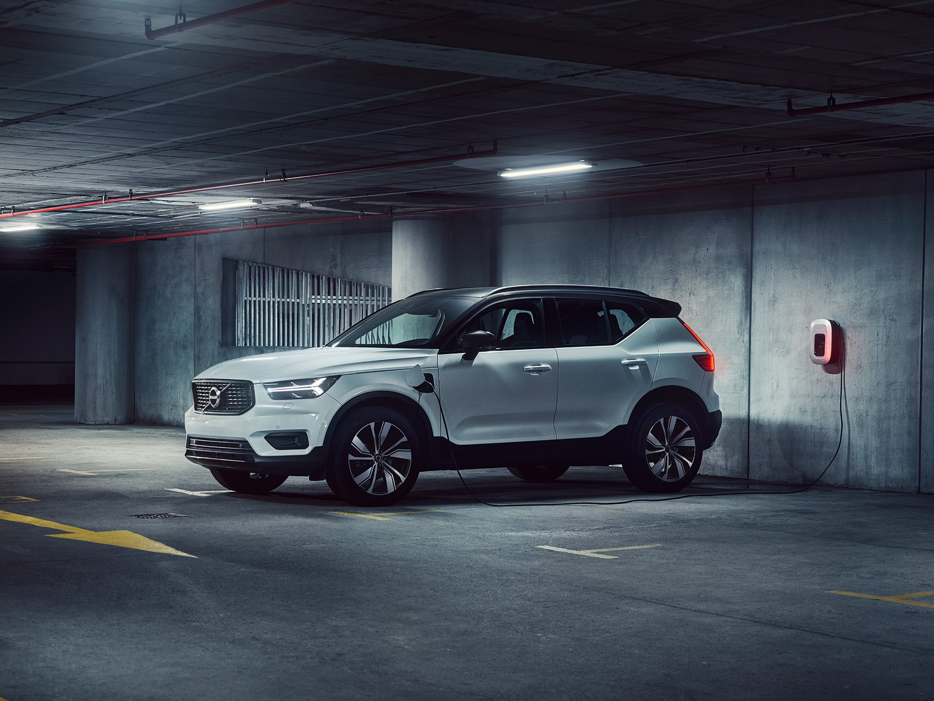 A white XC40 Recharge plug in hybrid SUV parked inside a garage and being charged.