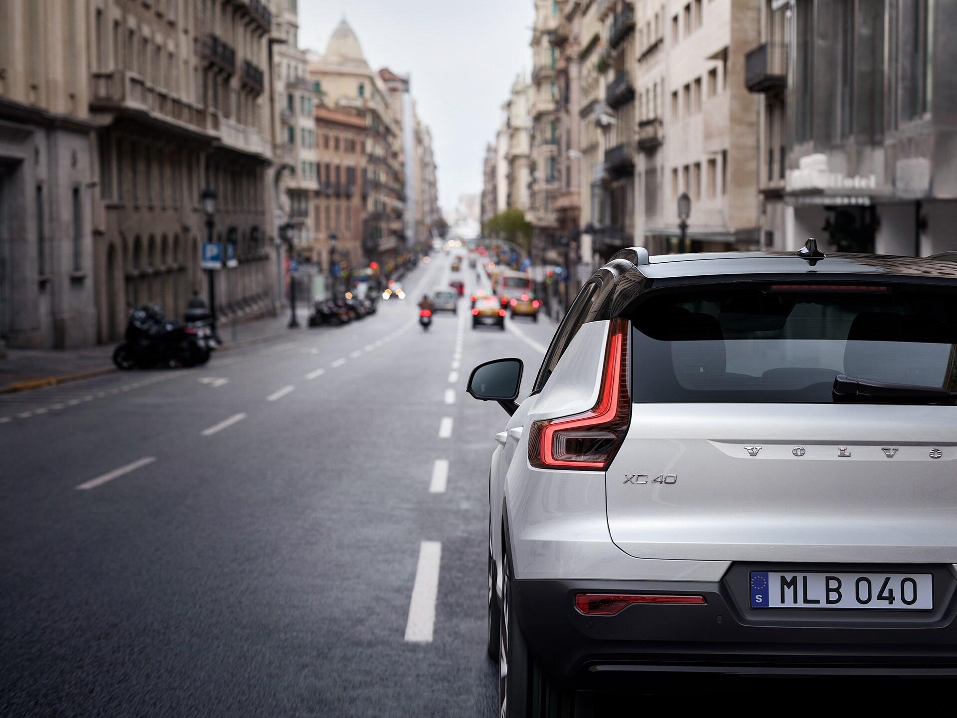 Ein weißer Volvo XC40 Mild-Hybrid fährt in der Stadt die Straße entlang.