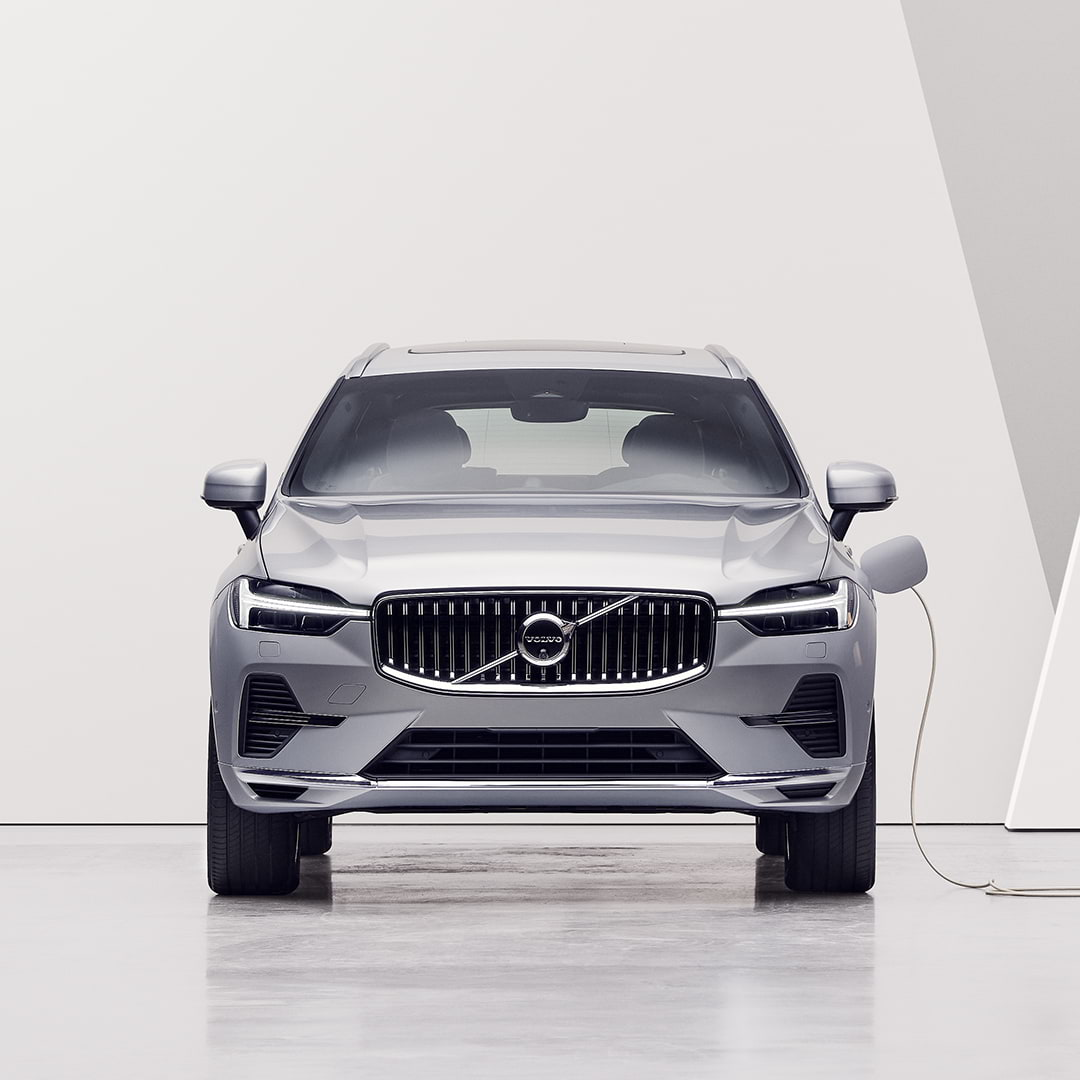 Eine Frau schaut sich einen Volvo XC60 Recharge an, der an eine Ladestation angeschlossen ist und aufgeladen wird.