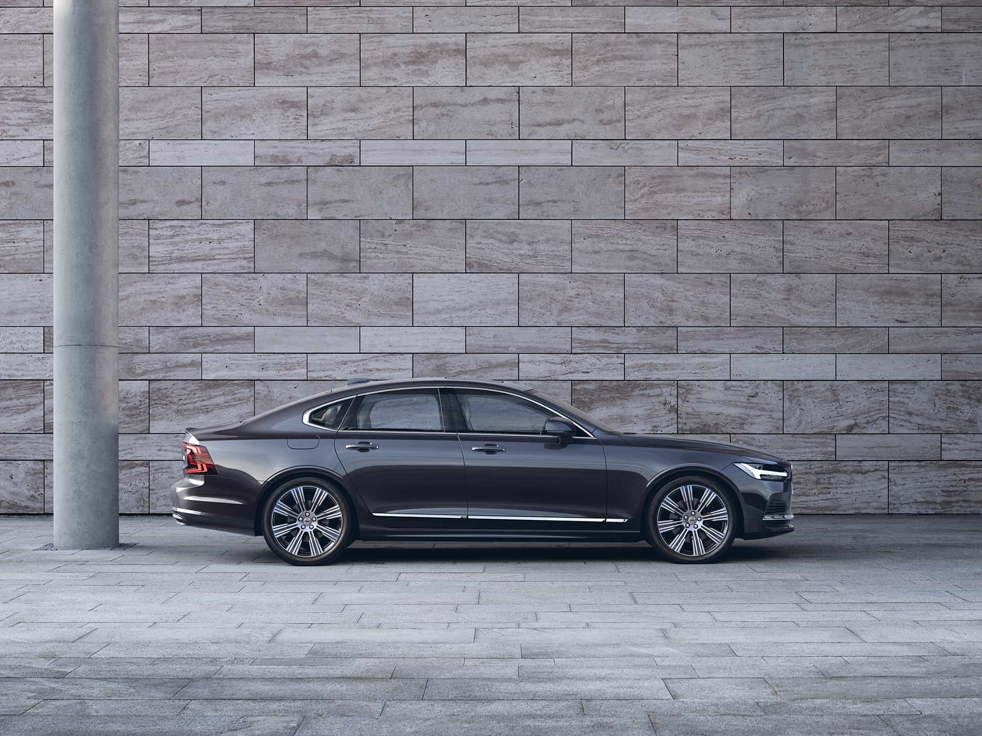 A dark Volvo S90 sedan is parked in front of a grey wall.