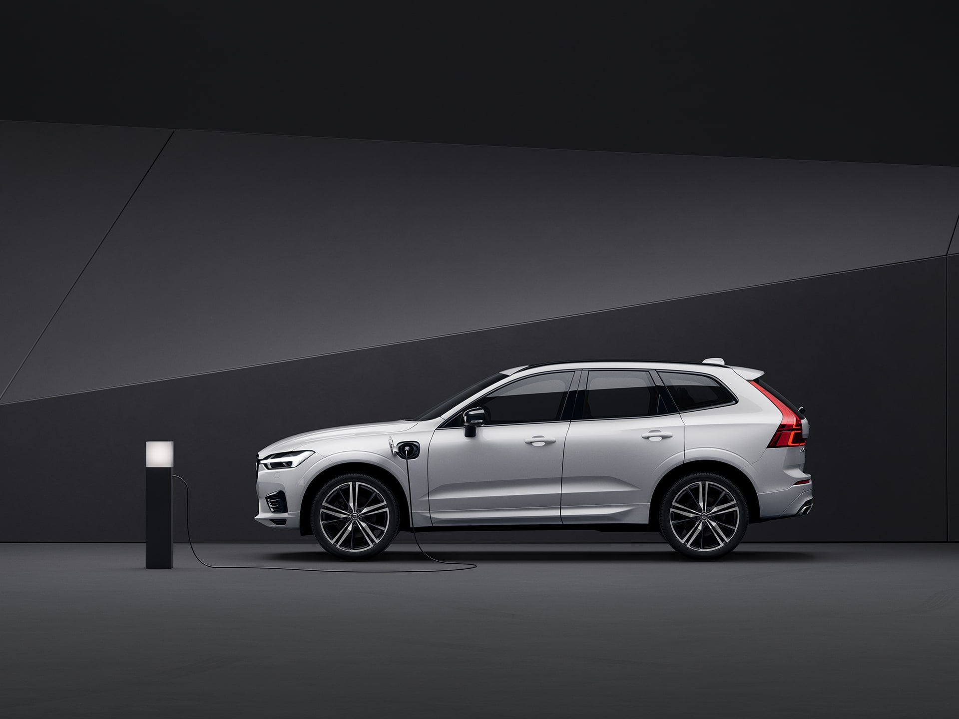 A white Volvo XC60 Recharge plug-in hybrid SUV charges in a black surrounding.