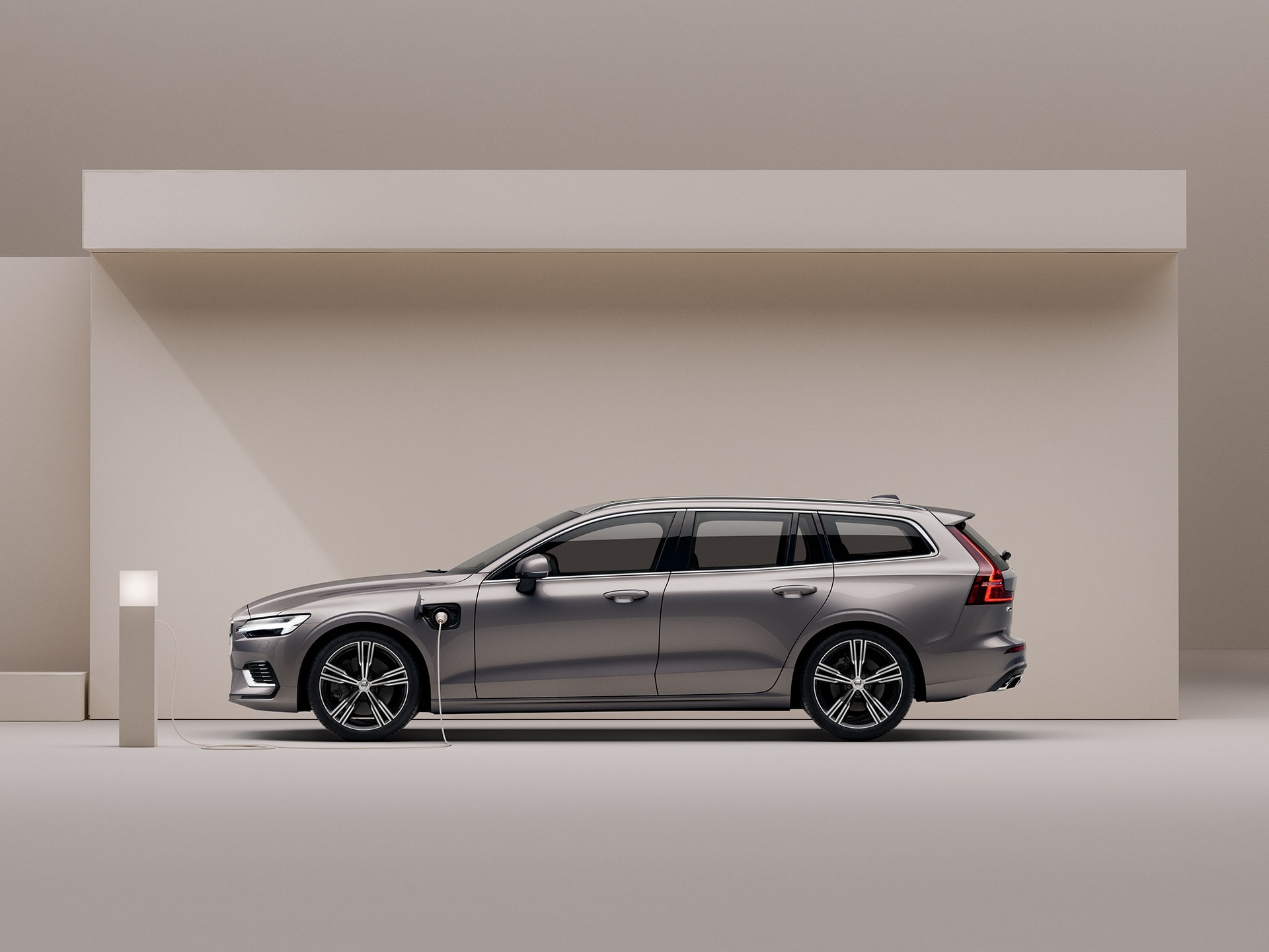 En beige Volvo V60 Recharge bliver ladet op i beige omgivelser