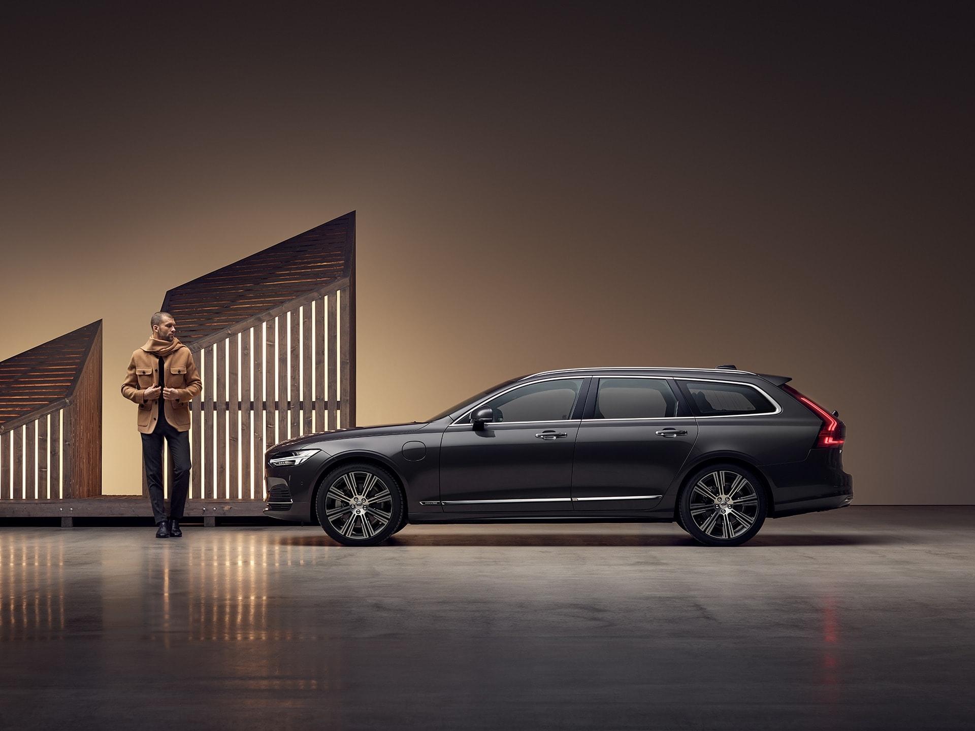 En mand i en brun jakke står ved siden af en Volvo V90 Recharge