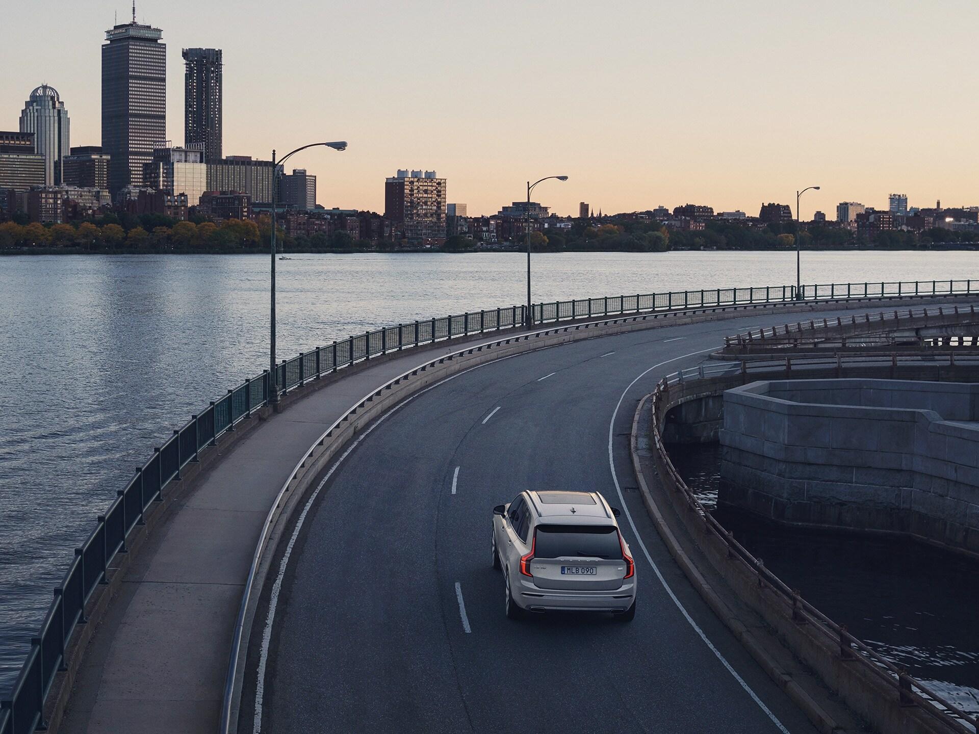 En Volvo XC90 Recharge i et vejsving langs vandet