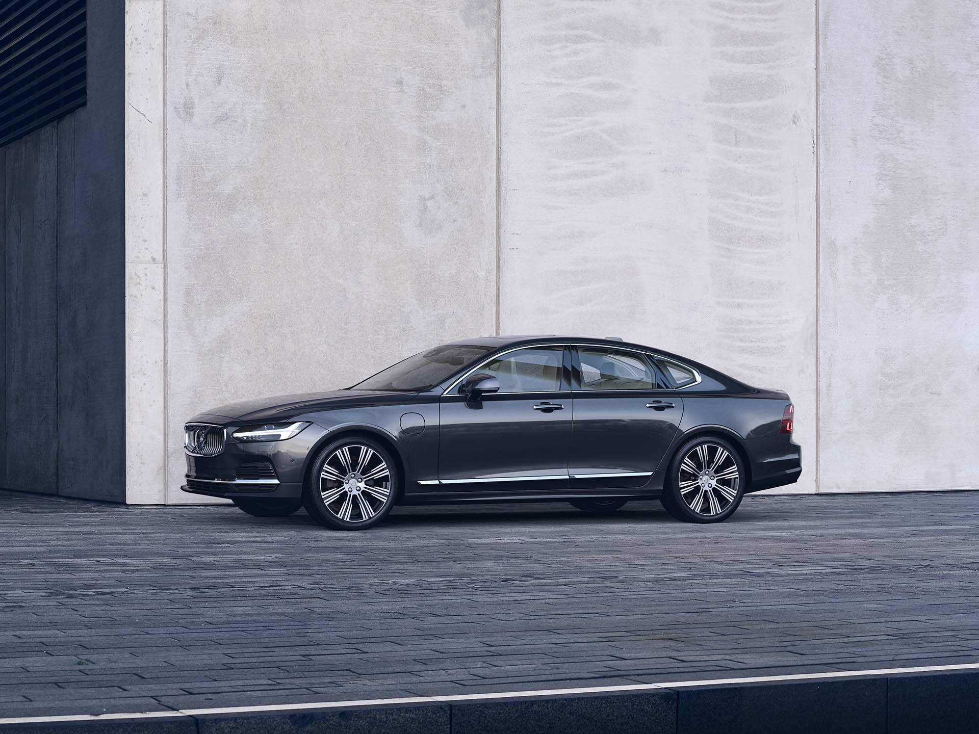 A Volvo Sedan Recharge parked outside in front of a big wall