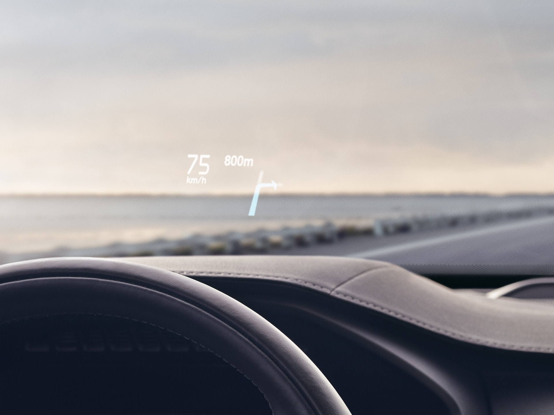 Inside a Volvo,head-up display showingdriving speedand navigationon the windshield.