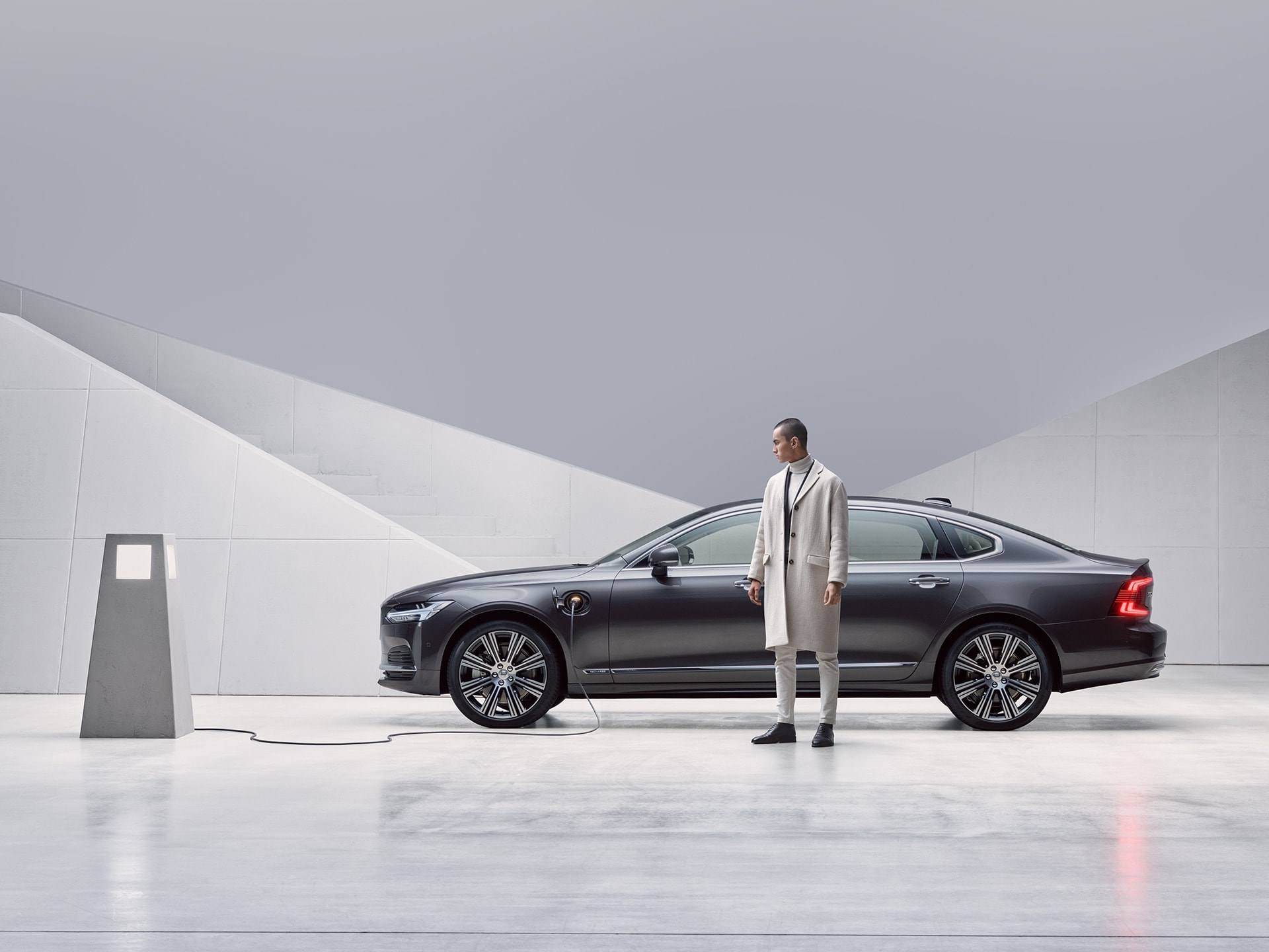A man is standing in front of his grey Volvo S90 Recharge, which is being charged.