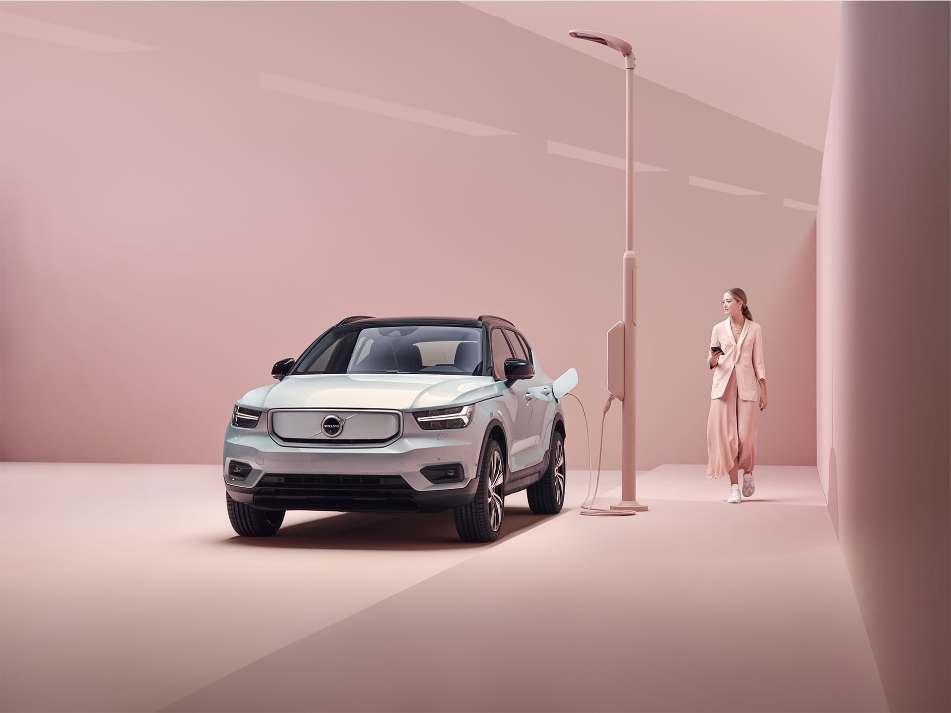A woman in pink walks next to a Volvo XC40 Recharge that gets charged next to a charging pole.