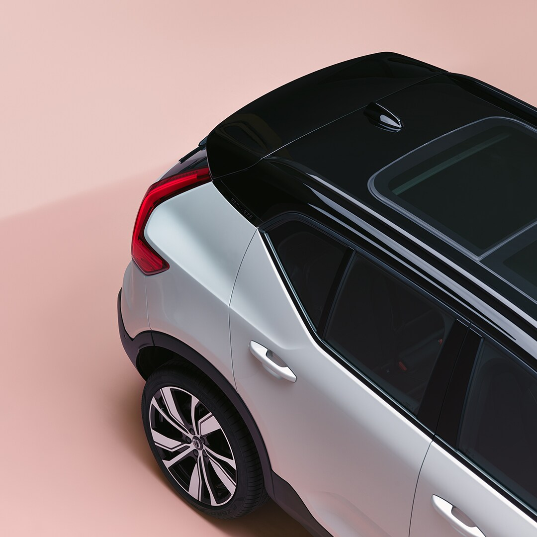 An XC40 Recharge from above, parked in a pink room.