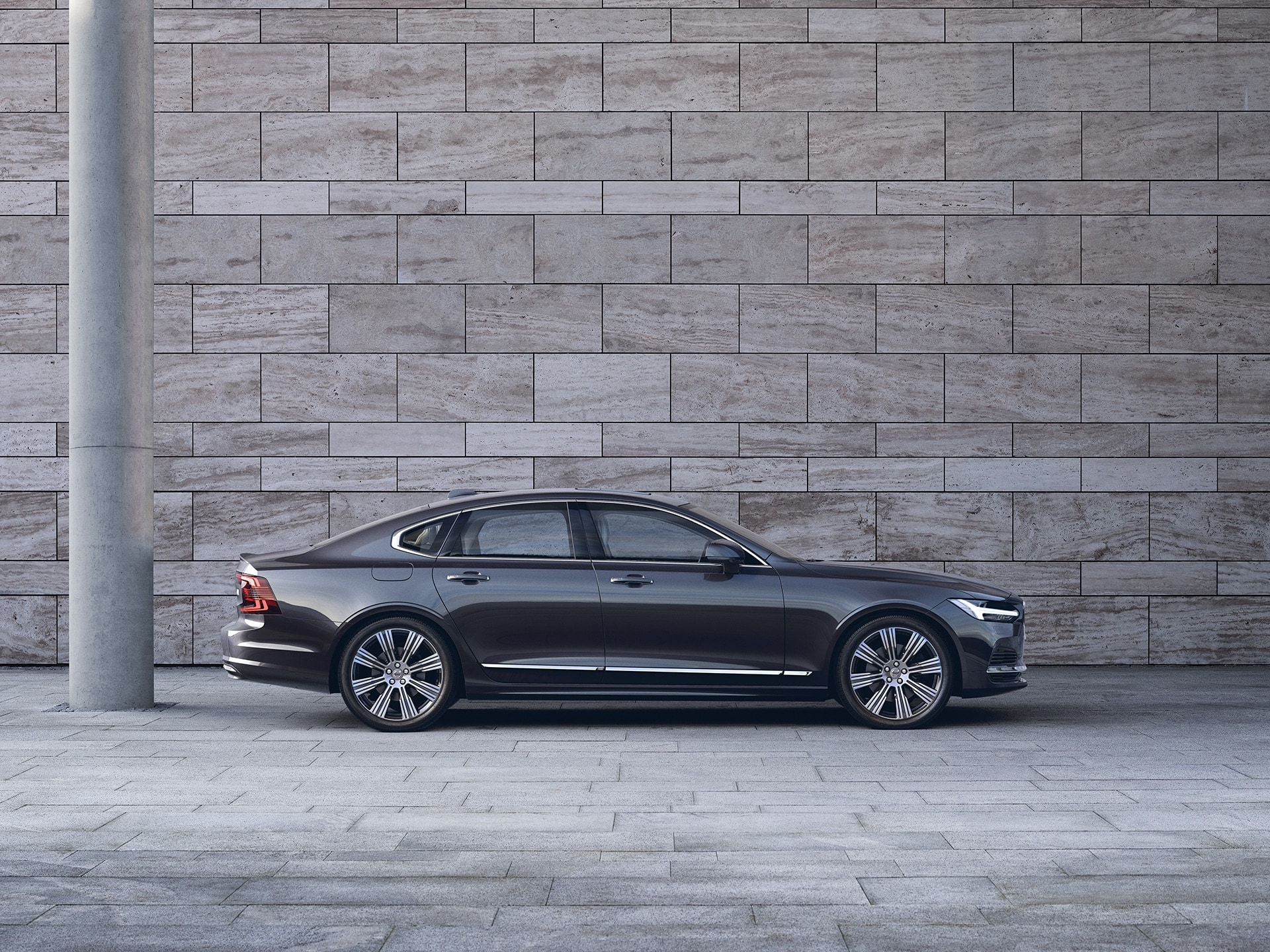 A dark Volvo S90 is parked in front of a grey wall.