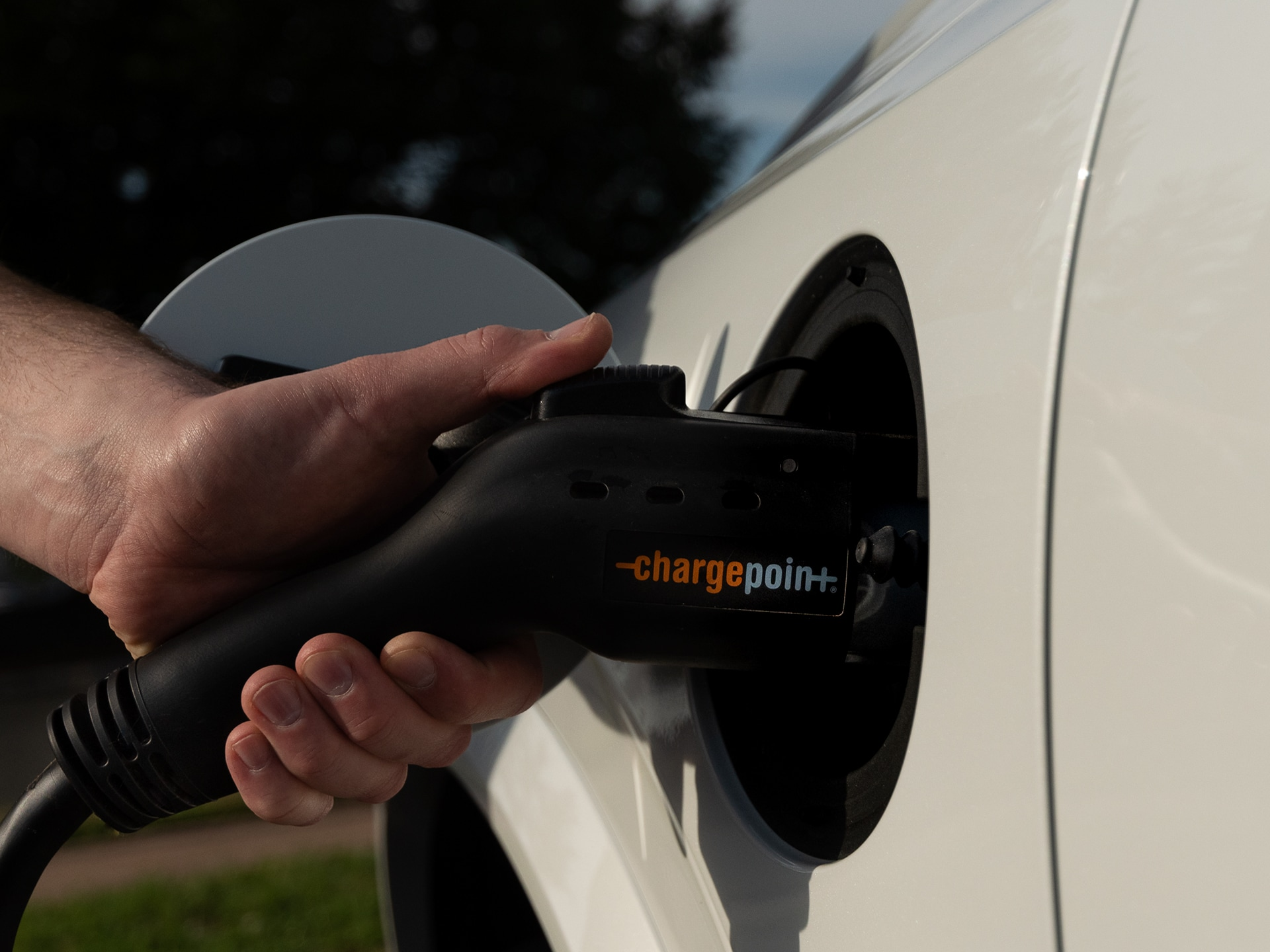 Close-up of driver's hand using a Plugsurfing charging key to activate charging station. In the middle ground, a left rear quarter-view of a new Volvo XC40 Recharge Pure Electric SUV, with charging plug inserted into car's charging port.