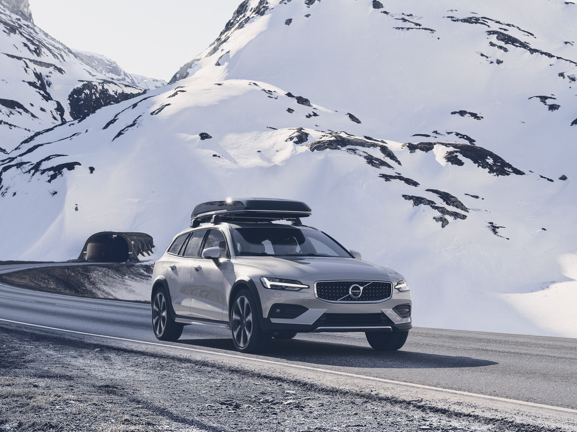 Volvo V60 Cross Country with roof box on a snowy mountain road