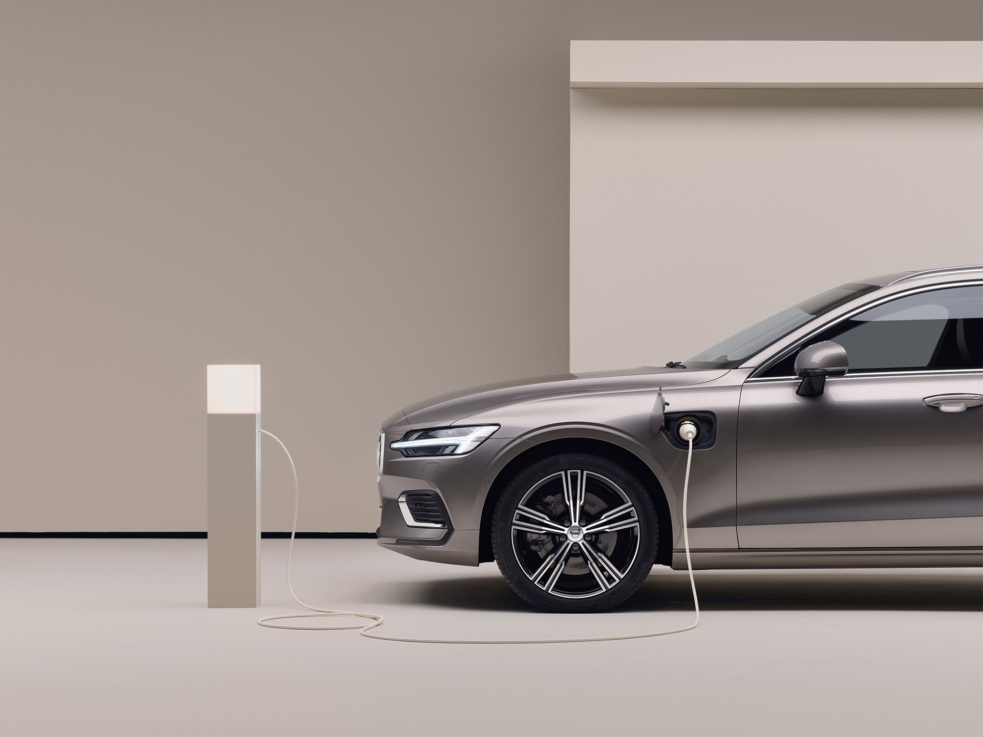 A parked grey Volvo wagon is plugged into a charging point
